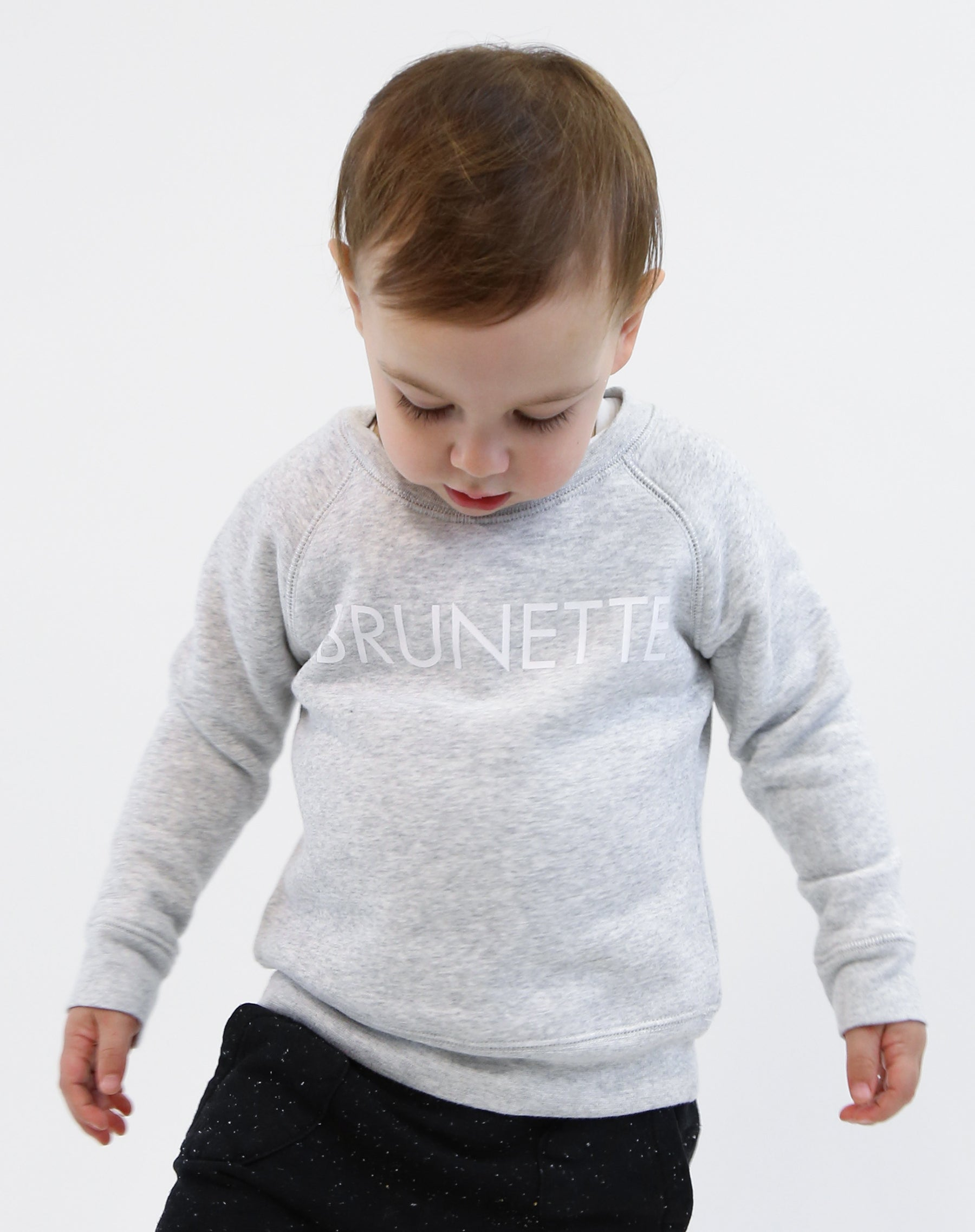 Photo of baby wearing the Brunette classic crew neck sweatshirt in pebble grey by Brunette the Label.