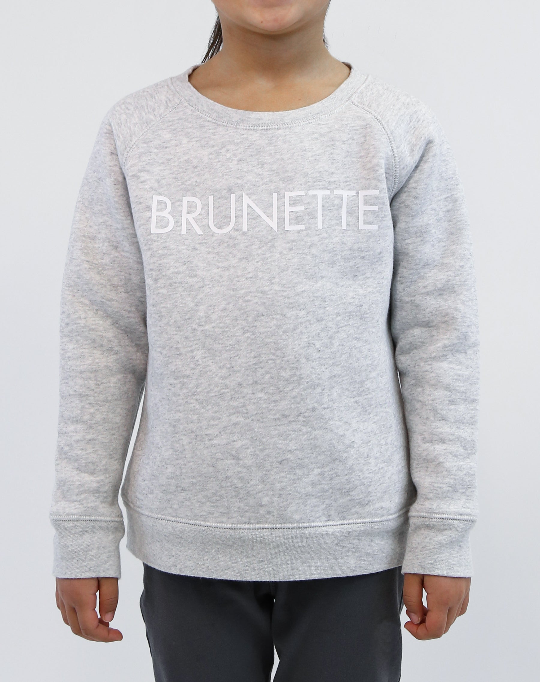 Photo of child wearing the Brunette classic crew neck sweatshirt in pebble grey by Brunette the Label.