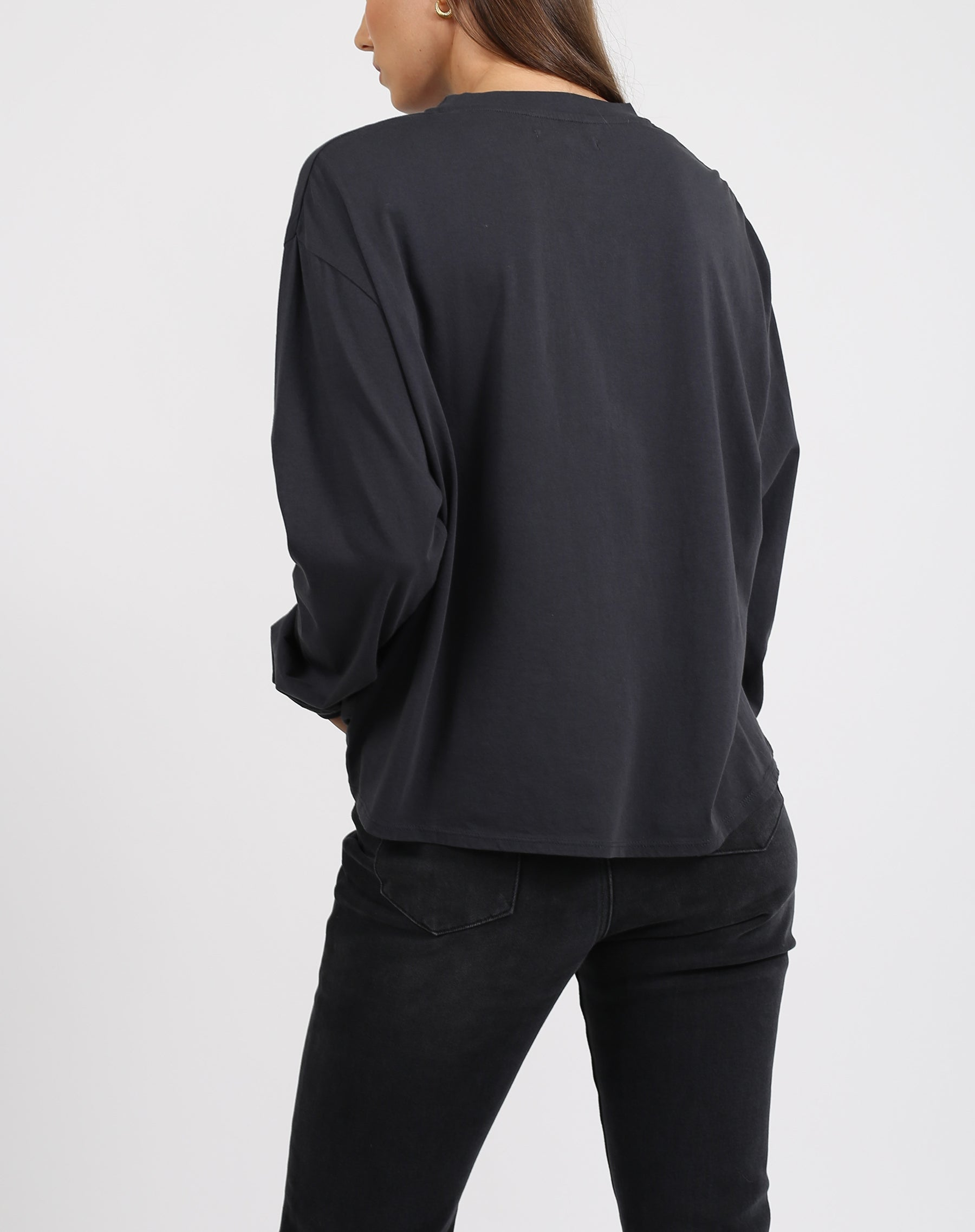 This is a photo of the back of a model wearing the 1981 mystic long sleeve boxy tee crew neck in charcoal by brunette the label.