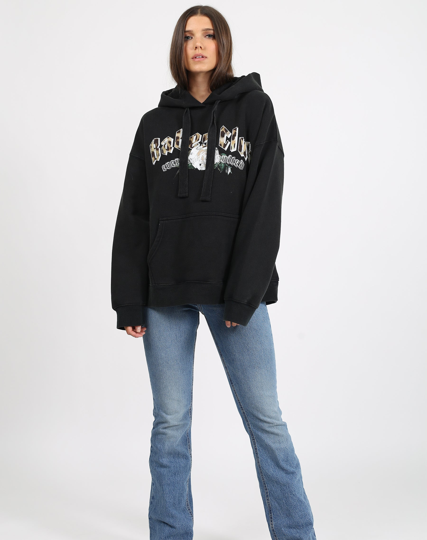 This is a photo of a model wearing the babes club big sister hoodie in acid wash black by brunette the label.
