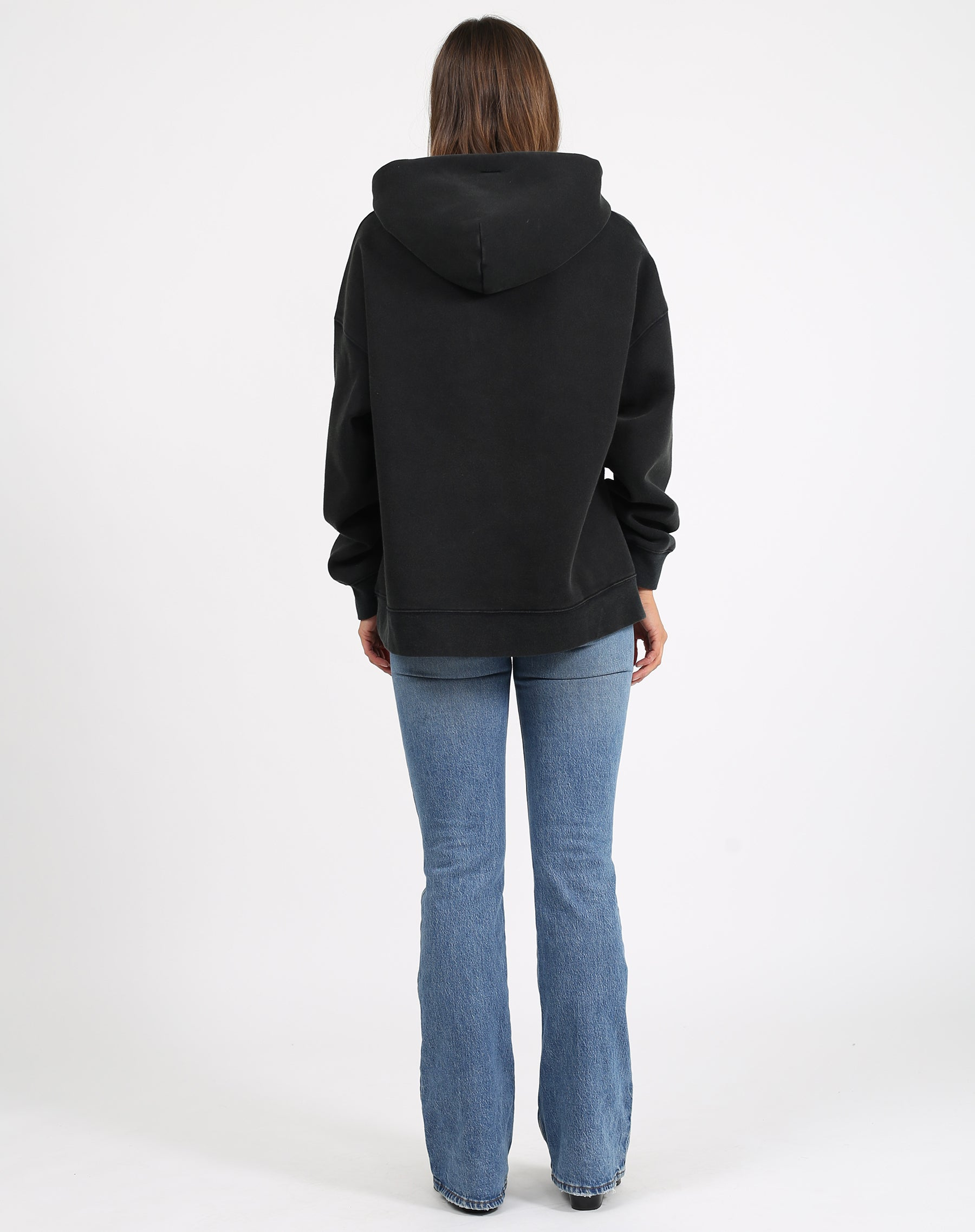 This is a photo of the back of a model wearing the babes club big sister hoodie in acid wash black by brunette the label.