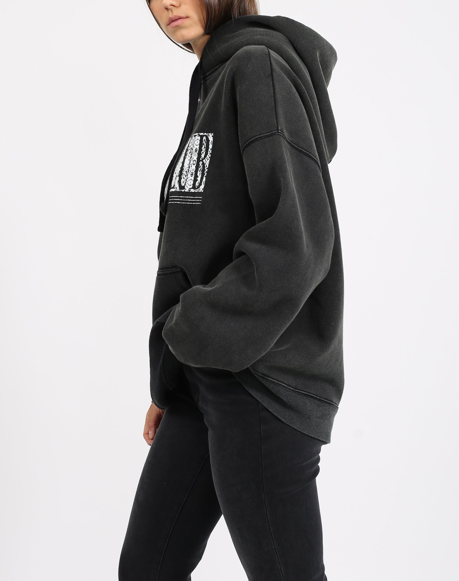 This is a photo of the side of a model wearing the babes club definition big sister hoodie in acid wash black by brunette the label.