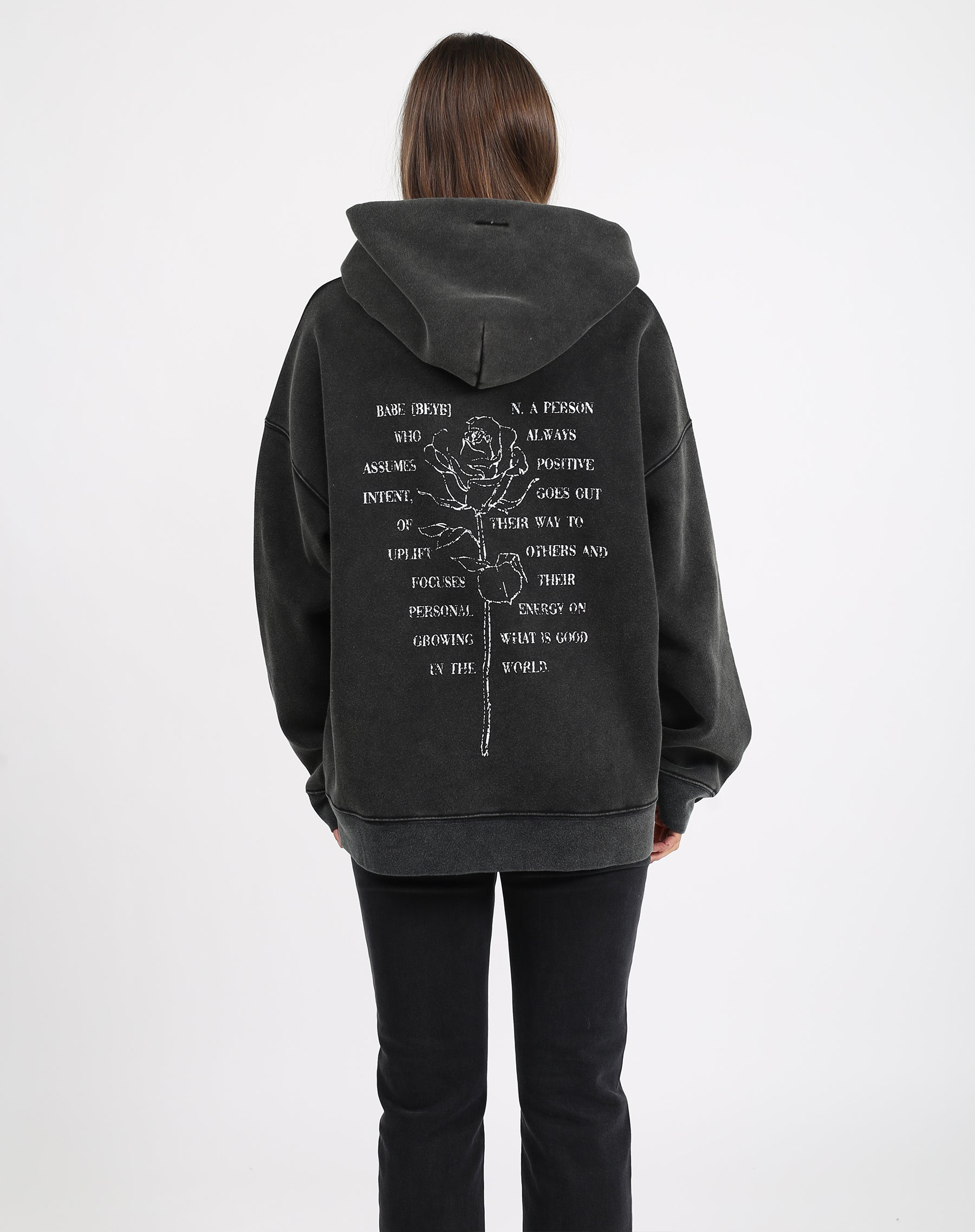 This is a photo of the back of a model wearing the babes club definition big sister hoodie in acid wash black by brunette the label.