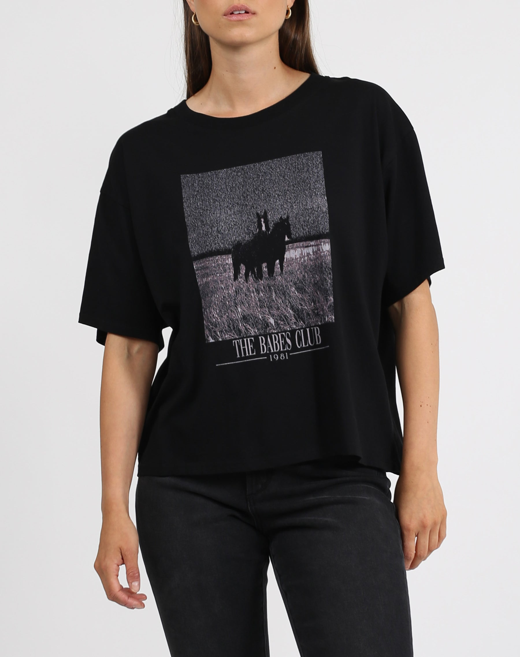 This is a photo of a model wearing the babes club horse boxy crew neck tee in black by brunette the label.