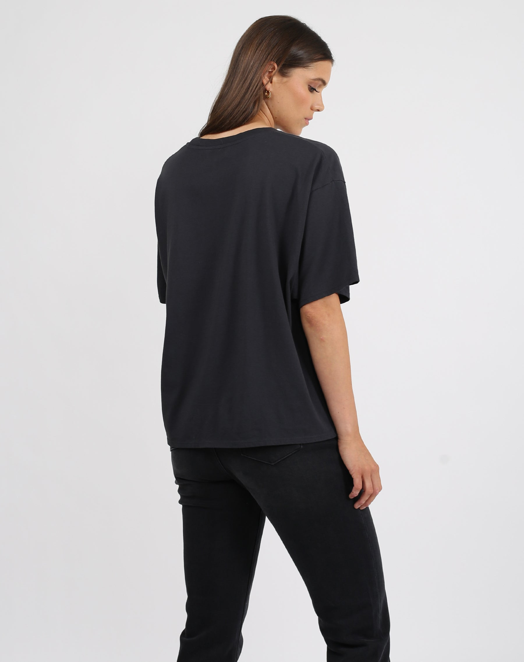 This is a photo of the back of a model wearing the babes club leopard boxy crew neck tee in black by brunette the label.