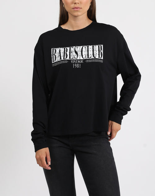 This is a photo of a model wearing the babes club long sleeve boxy tee in black by brunette the label.