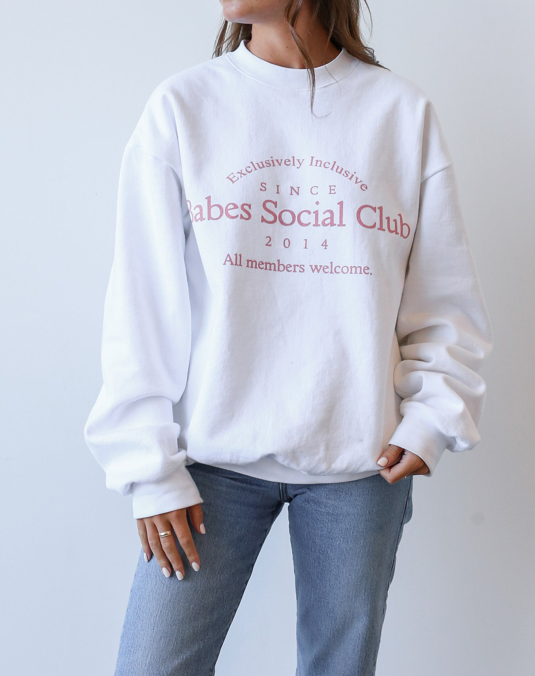 This is an Ecommerce photo of the Babes Social Club Crew Neck Sweatshirt in white and pink by Brunette the Label.