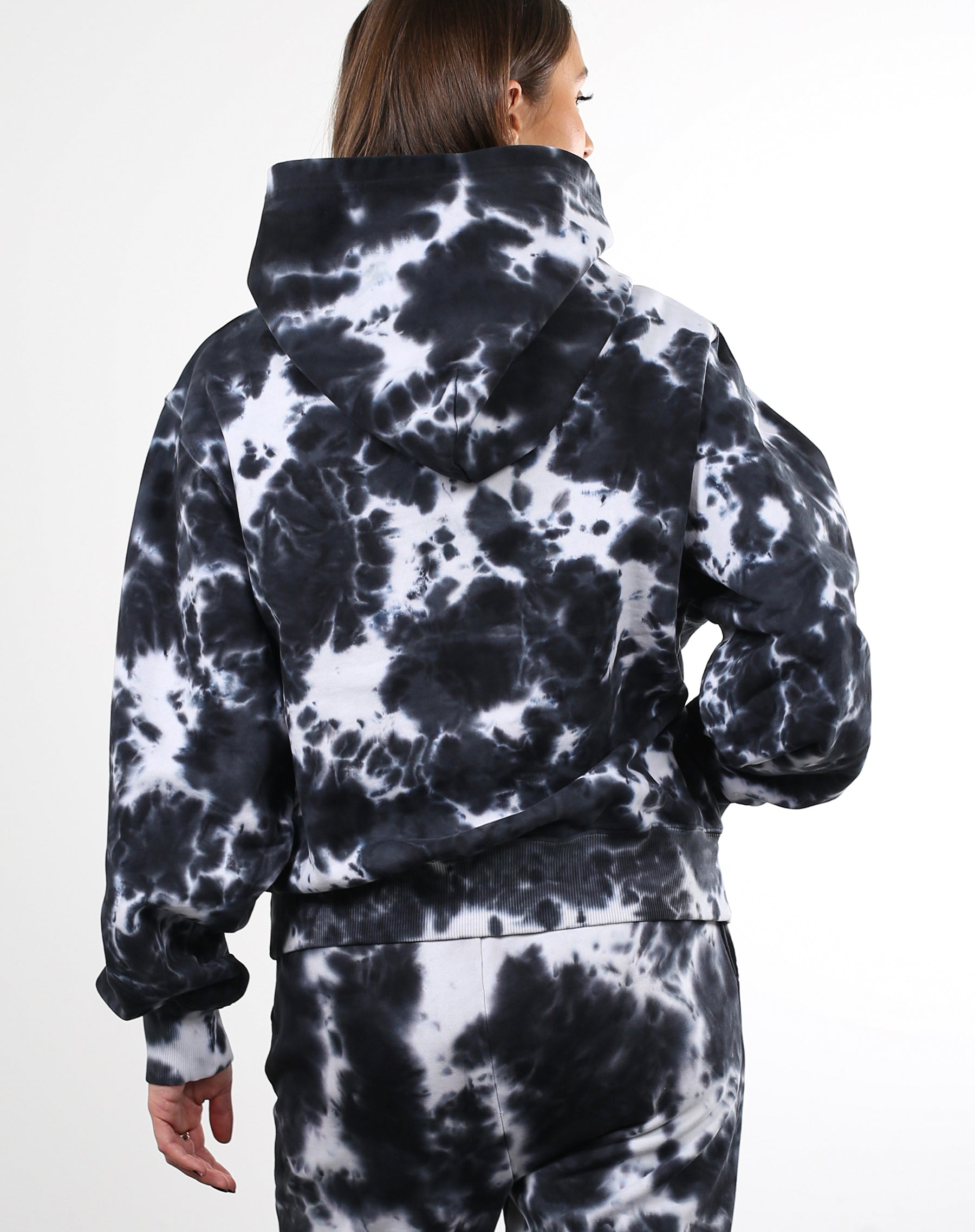 This is a photo of the back of a model wearing the Best Friend Hoodie in Black Marble Dye by Brunette the Label.