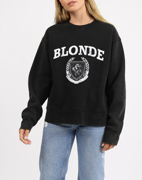 This is a photo of a model wearing the blonde varsity step sister crew neck sweater in acid wash black by brunette the label.