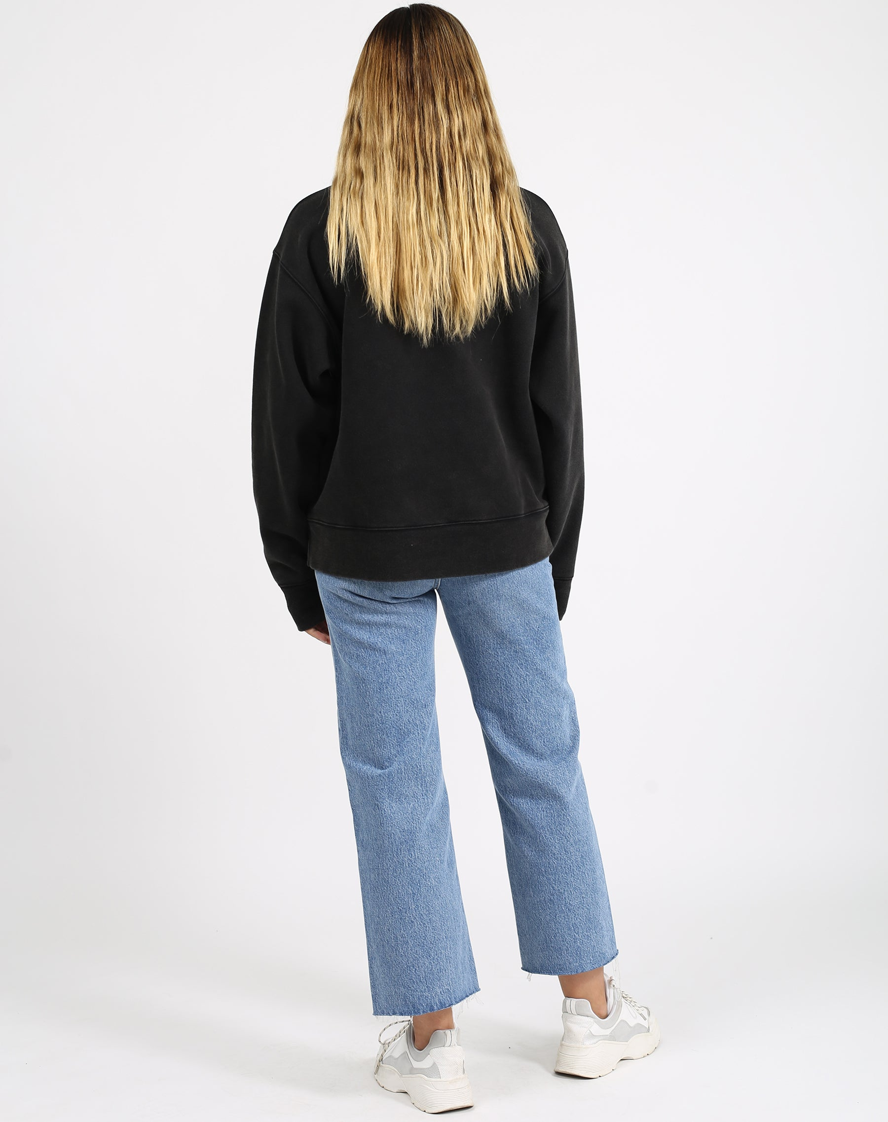 This is a photo of a the back of a model wearing the blonde varsity step sister crew neck sweater in acid wash black by brunette the label.