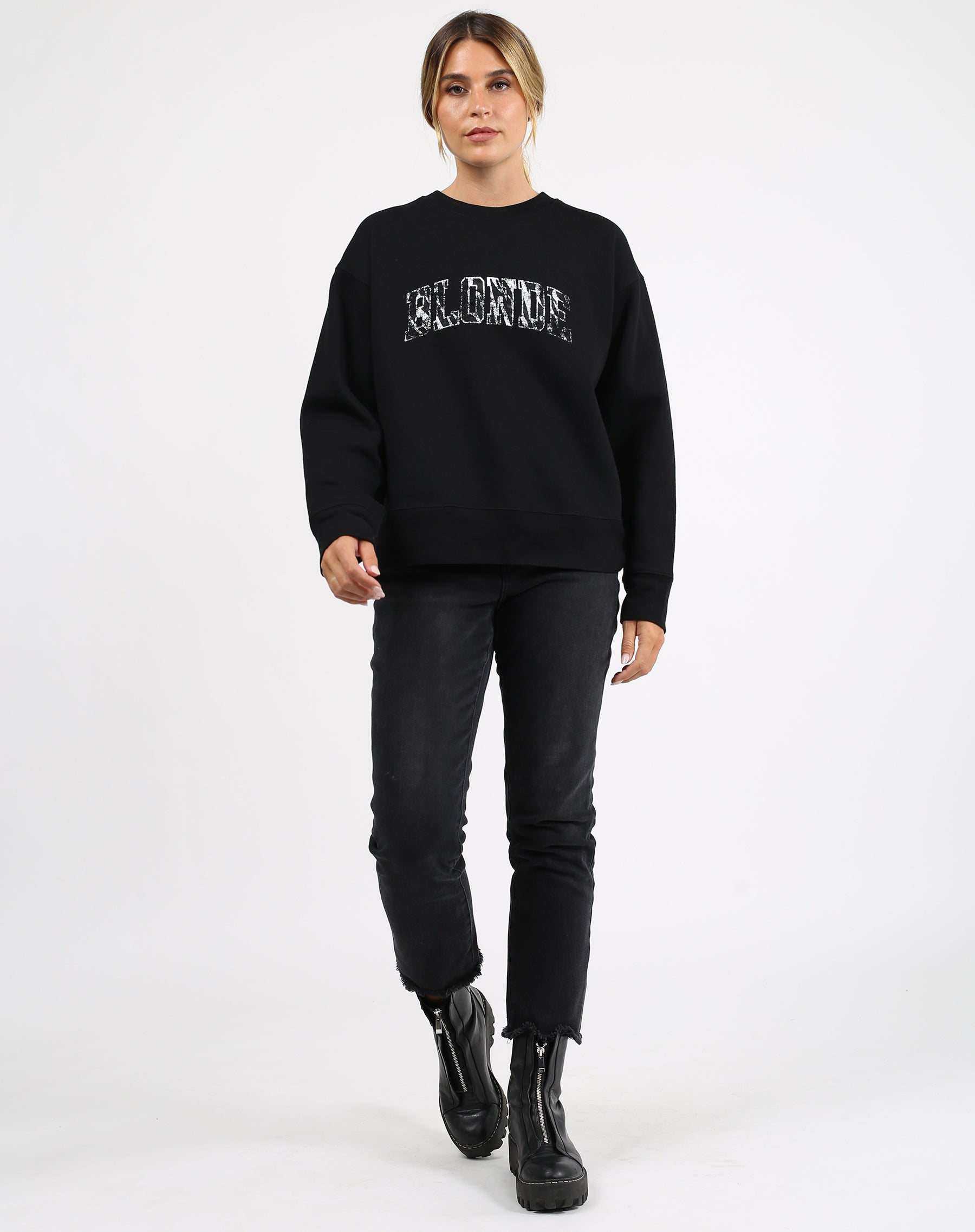 This is an image a model wearing the Blonde Zebra Varsity Step Sister Crew Neck Sweatshirt in Black by Brunette the Label.
