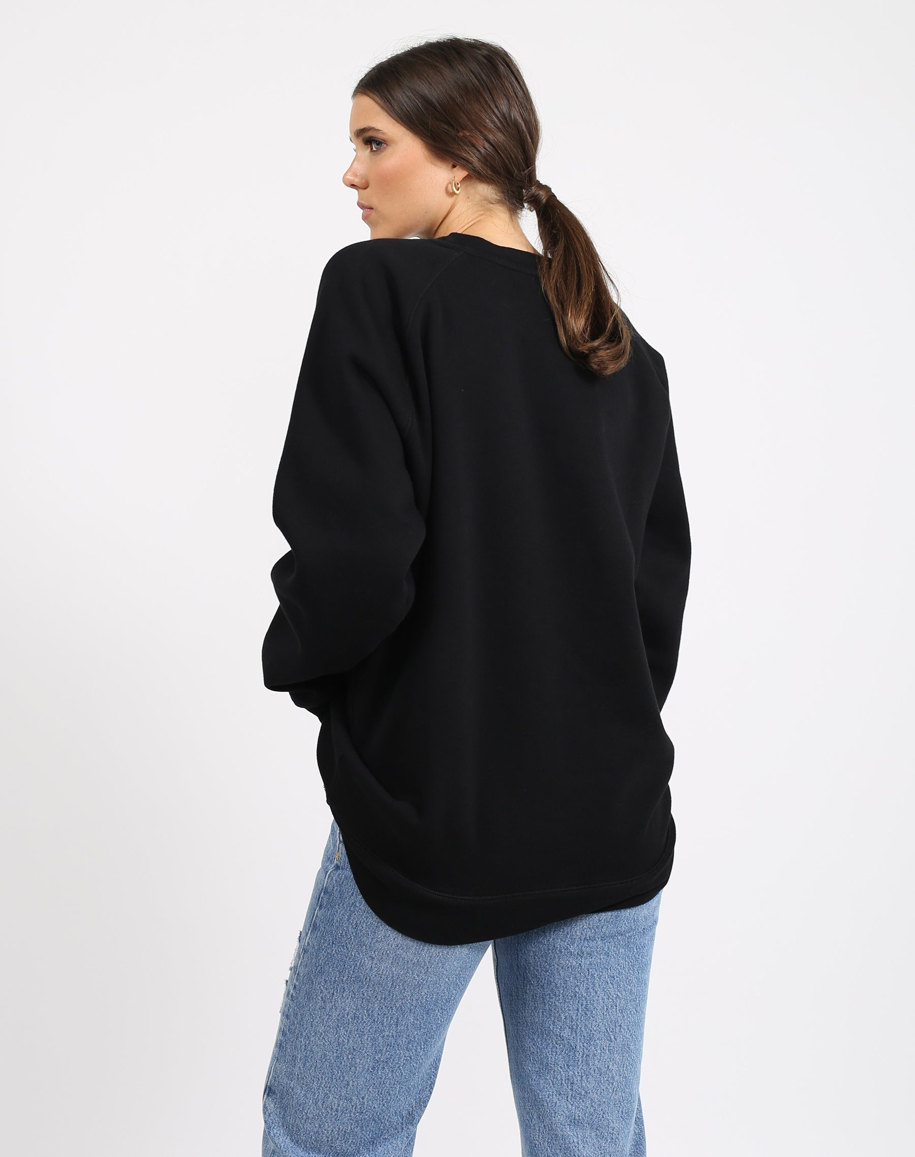 This is a photo of the back of a model wearing the Lounge Jet Black Big Sister Crew Neck Sweatshirt in Black by Brunette the Label.'