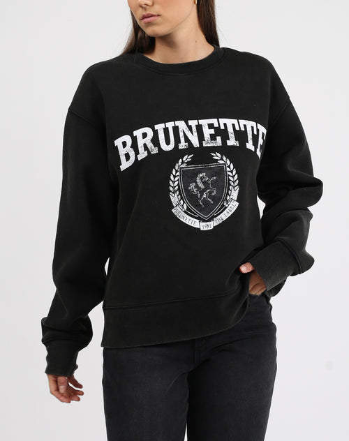 This is a photo of a model wearing the brunette varsity step sister crew neck sweater in acid wash black by brunette the label.