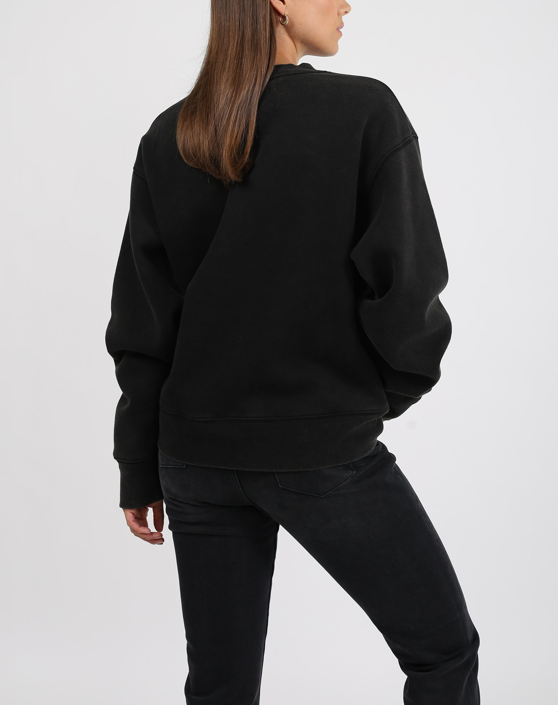 This is a photo of the back of a model wearing the brunette varsity step sister crew neck sweater in acid wash black by brunette the label.