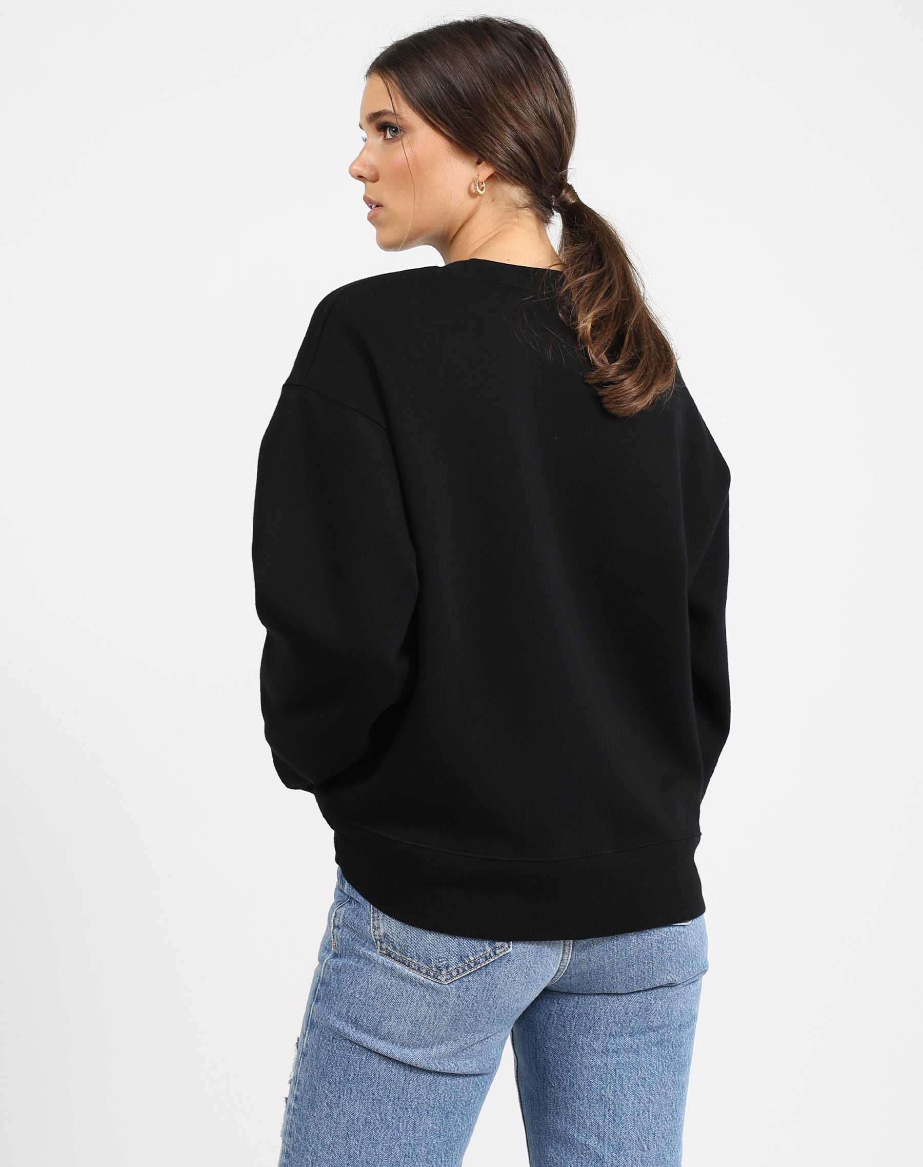 This is an image of the back of a model wearing the Jet Black Zebra Varsity Step Sister Crew Neck Sweatshirt in Black by Brunette the Label.