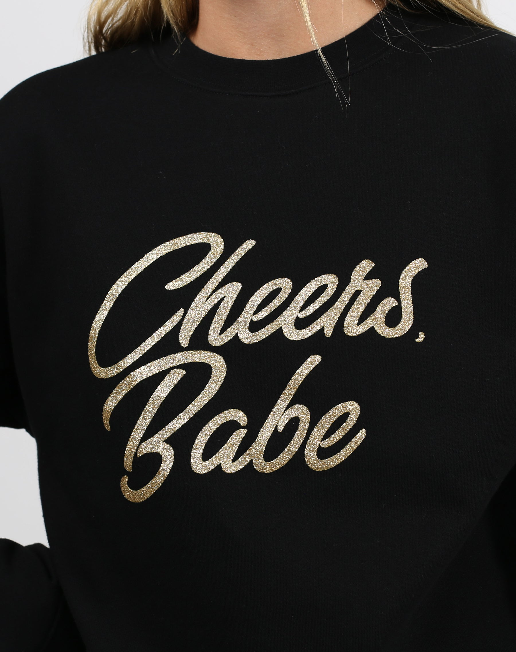 This is a photo of a model wearing the Cheers Babe Gold Glitter Classic Crew Neck Sweatshirt in Black by Brunette the Label.
