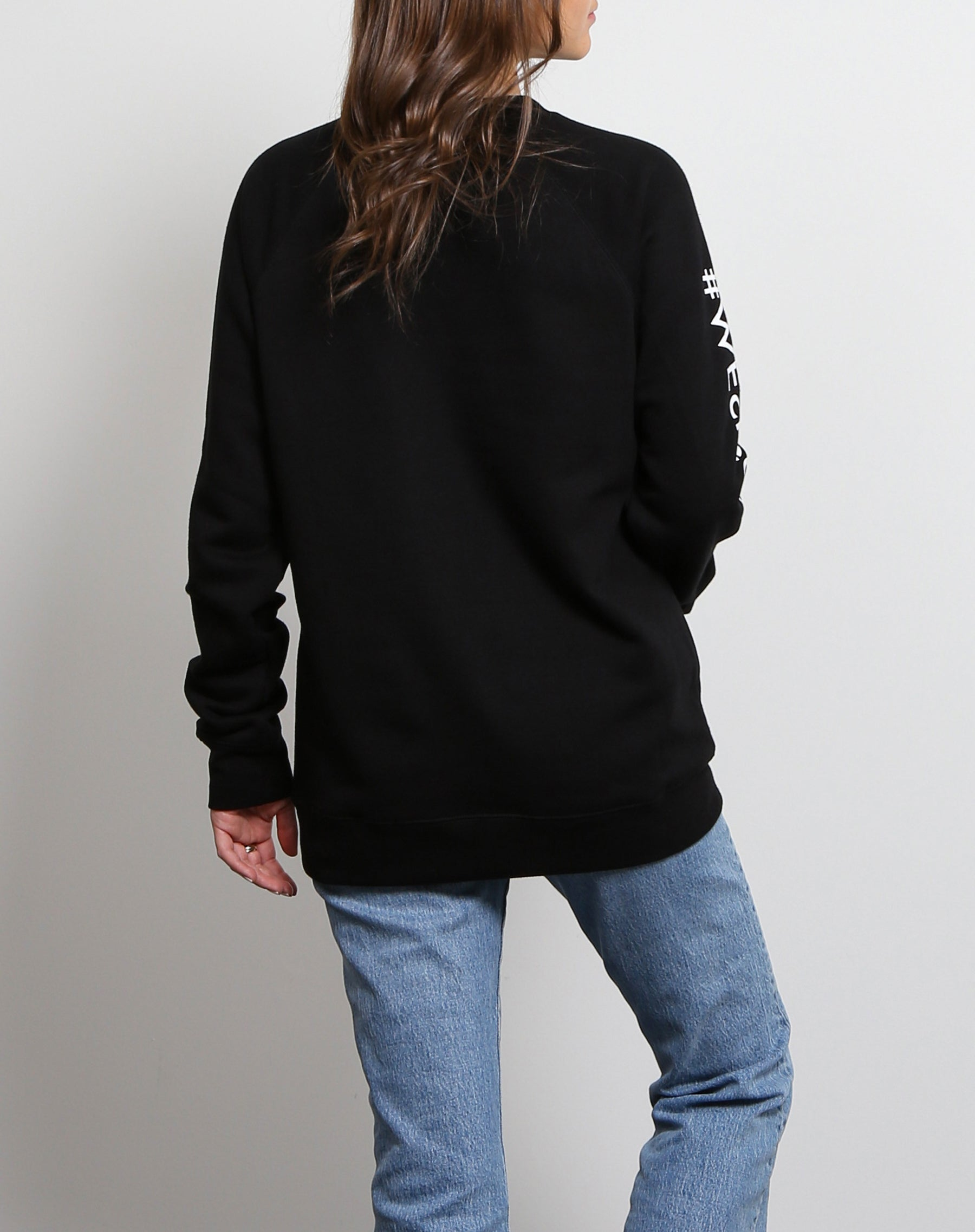 This is a photo of a the back of a model wearing the FWE We Create BC Babes Supporting Babes Classic Crew Neck Sweatshirt in Black by Brunette the Label.
