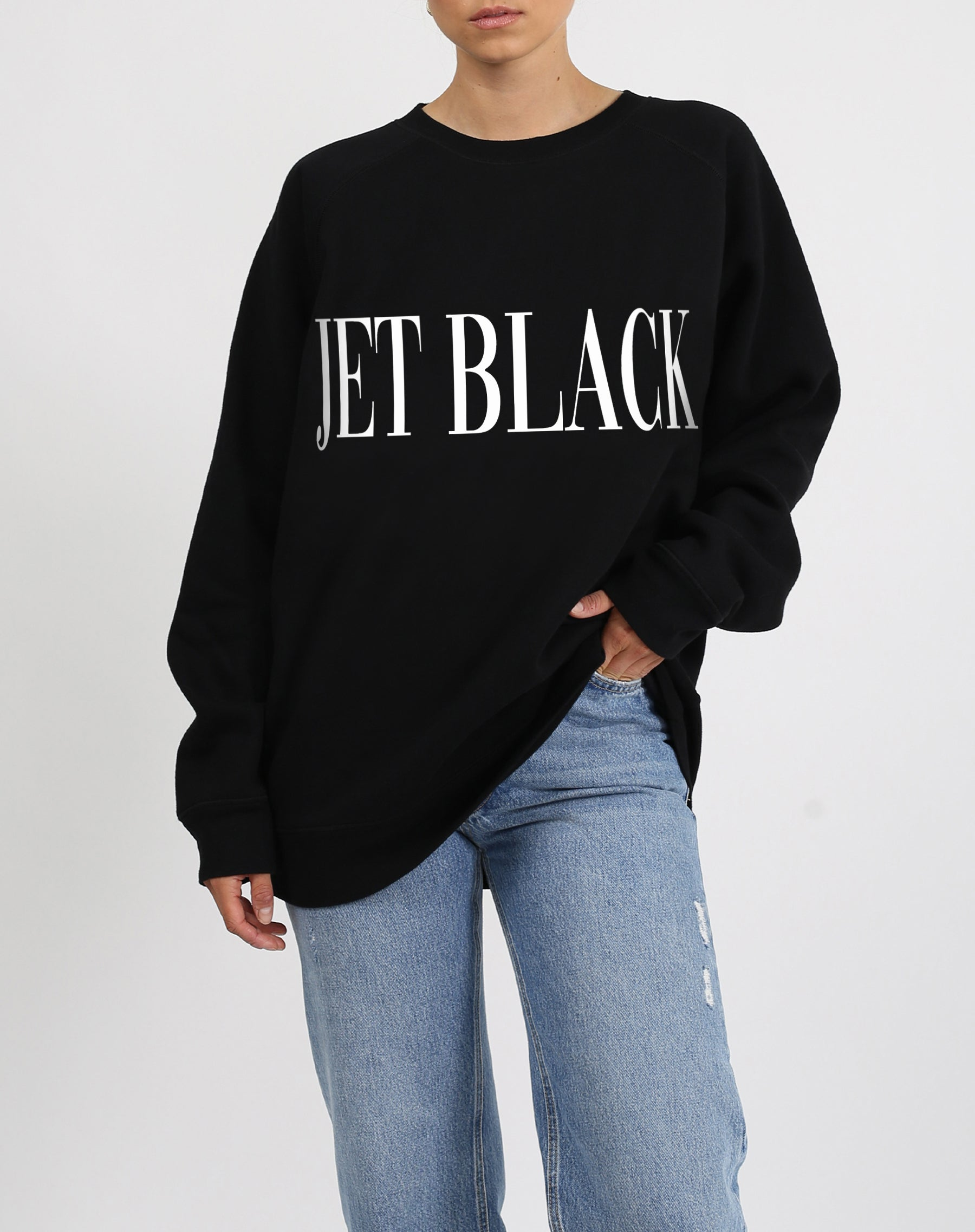 This is a photo of a model wearing the Lounge Jet Black Big Sister Crew Neck Sweatshirt in Black by Brunette the Label.'