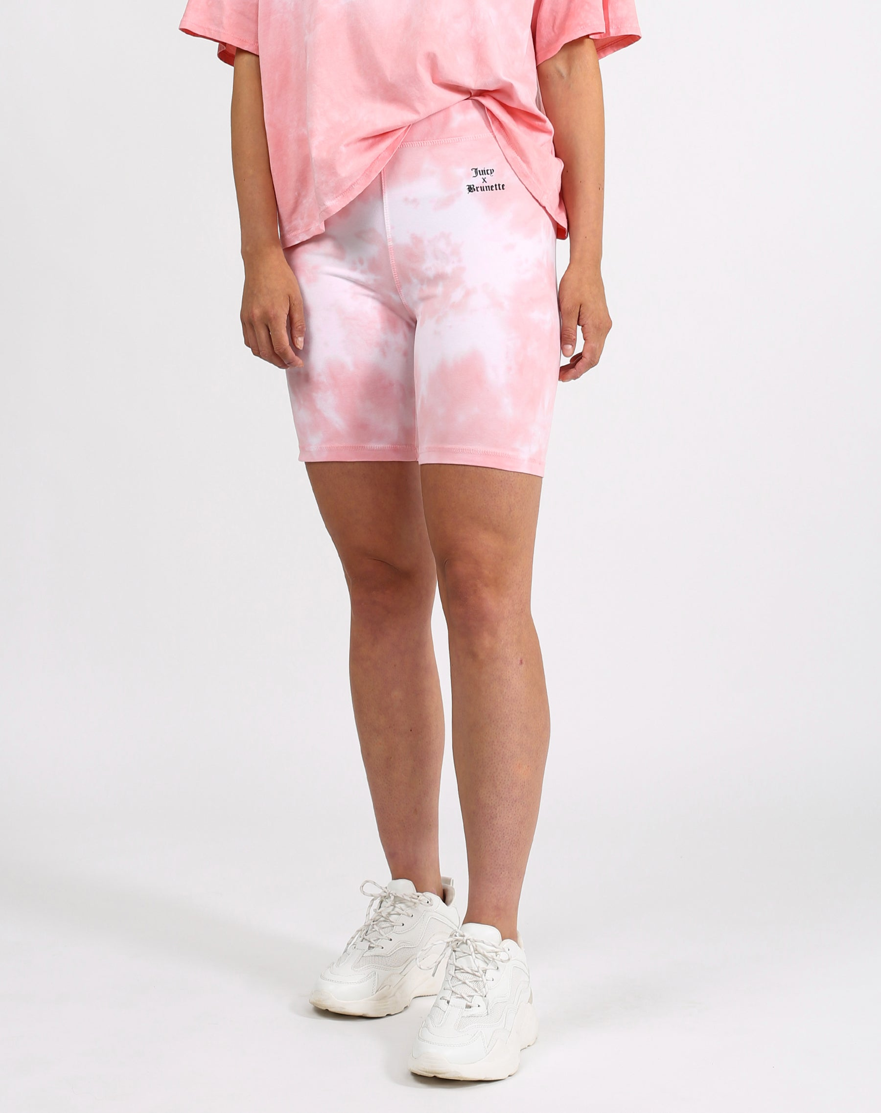 This is a photo of a model wearing the biker shorts in pink marble by Brunette the Label x Juicy Couture.