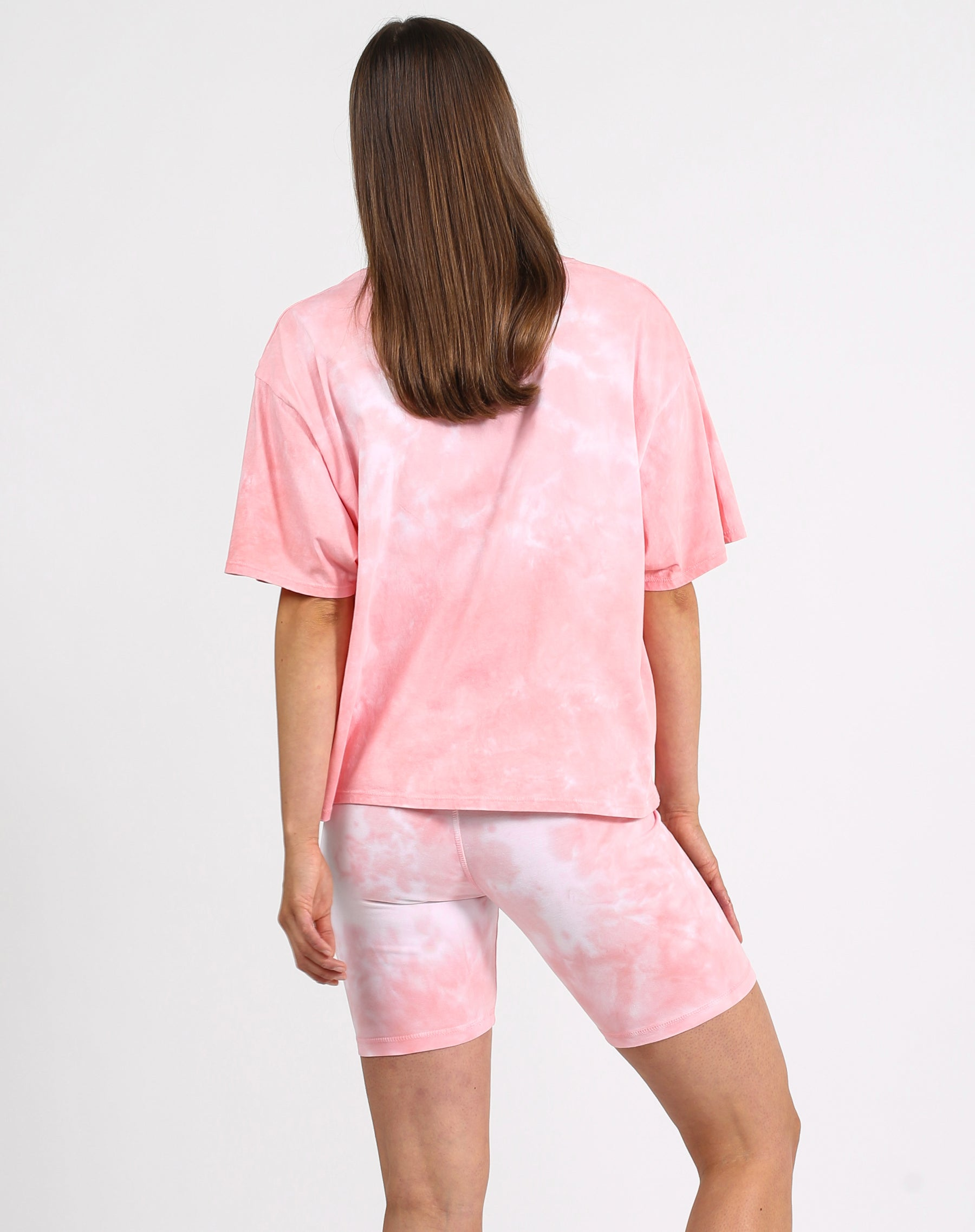 This is a photo of a model wearing the jet black boxy retro tee in pink marble by Brunette the Label x Juicy Couture.