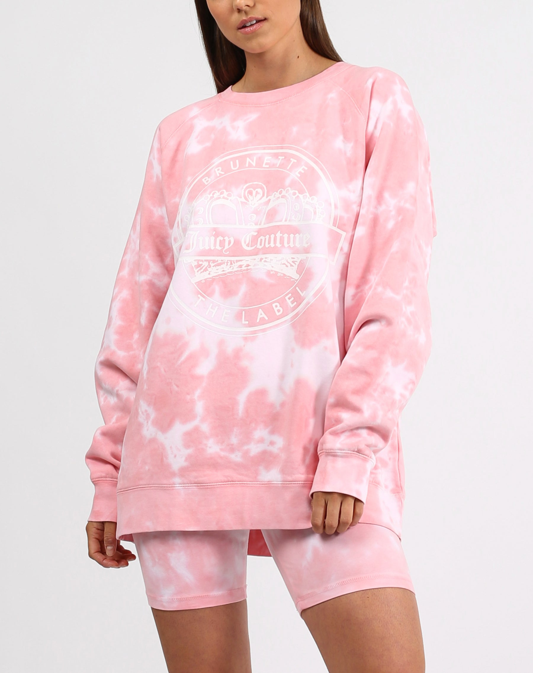 This is a photo of a model wearing the varsity big sister crew neck sweatshirt in pink marble by Brunette the Label x Juicy Couture.