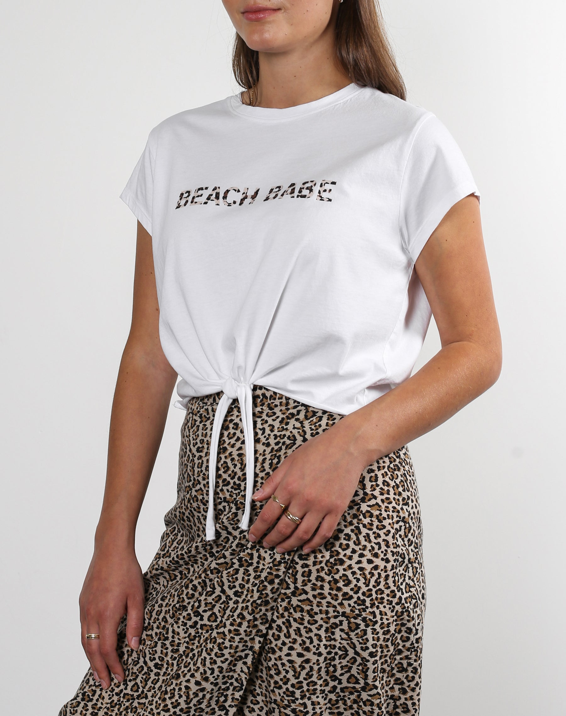 This is an Ecommerce photo of a model wearing the White Beach Babe tee from the koy restort collection from brunette the label