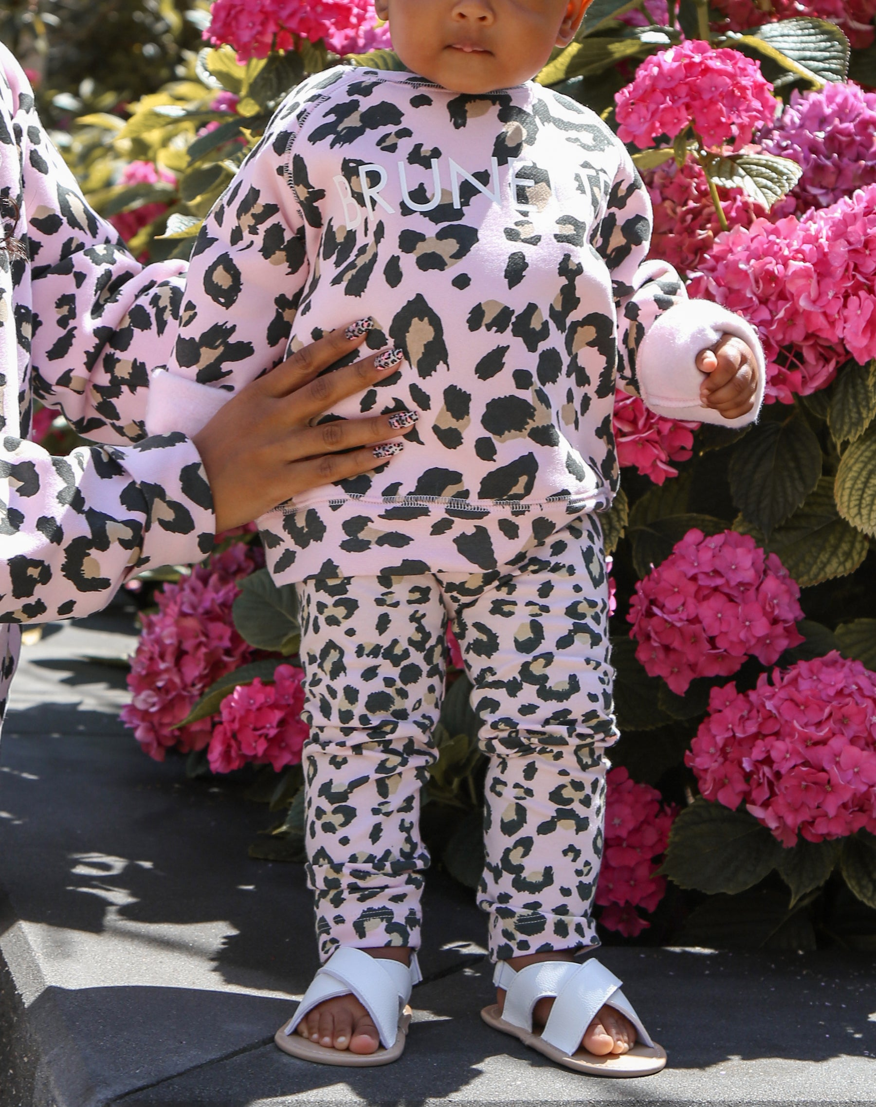 This is a photo of a model wearing the little babes basic leggings in pink leopard by brunette the label.