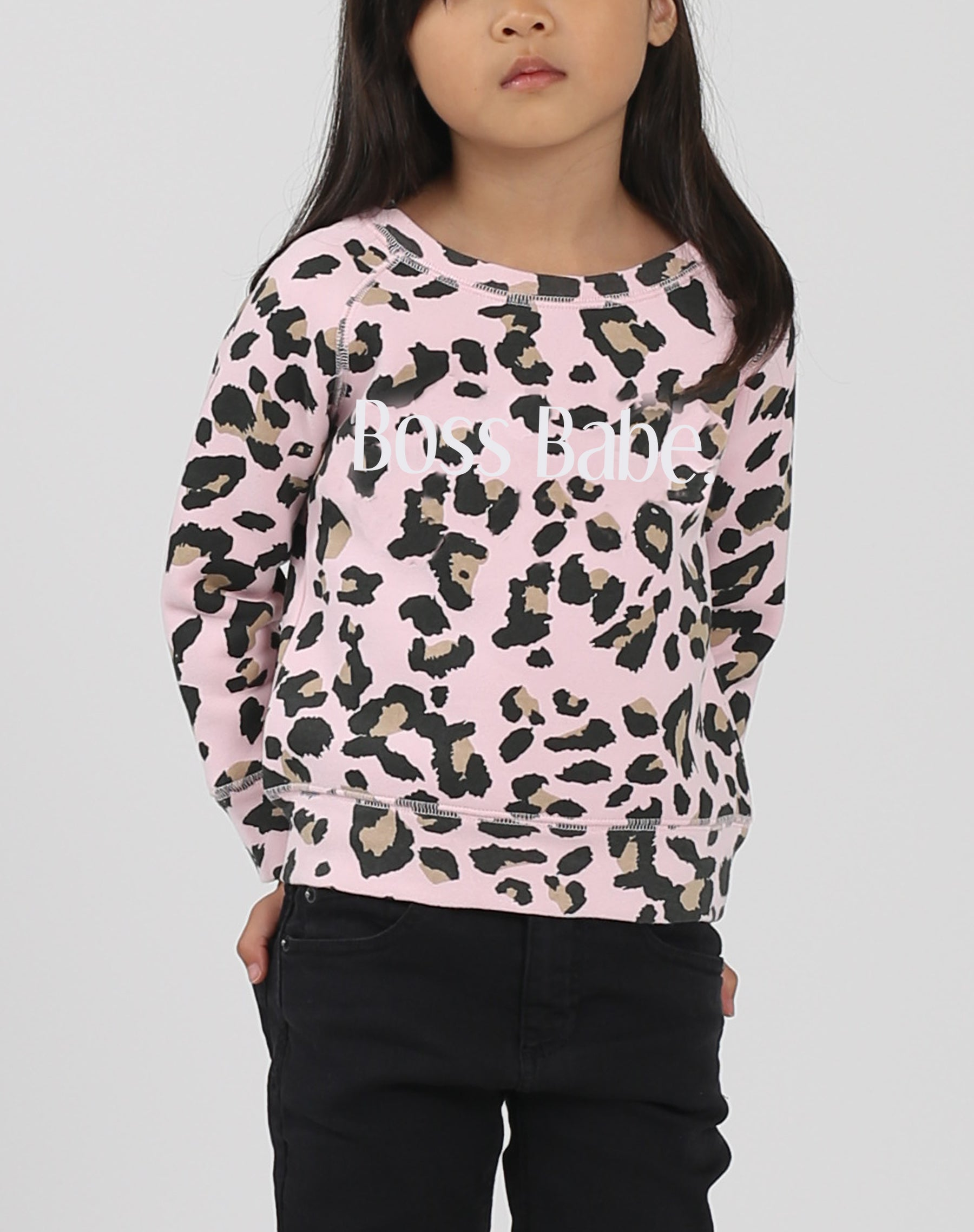 This is a photo of a model wearing the little babes boss babe crew neck sweatshirt in pink leopard by brunette the label.