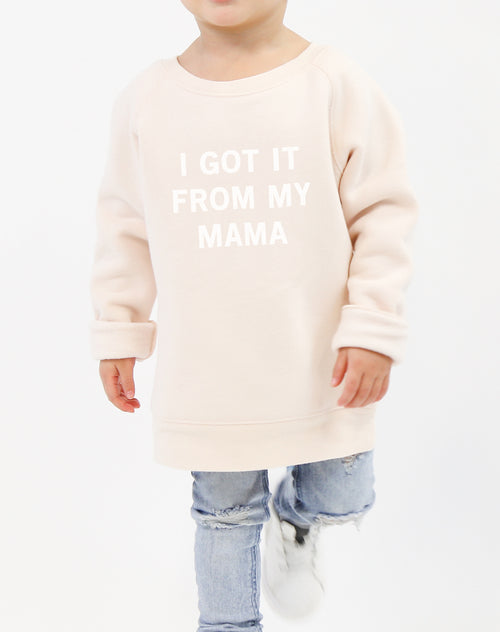 Photo of child wearing the I Got It From My Mama classic crew neck sweatshirt in peach crush by Brunette the Label.