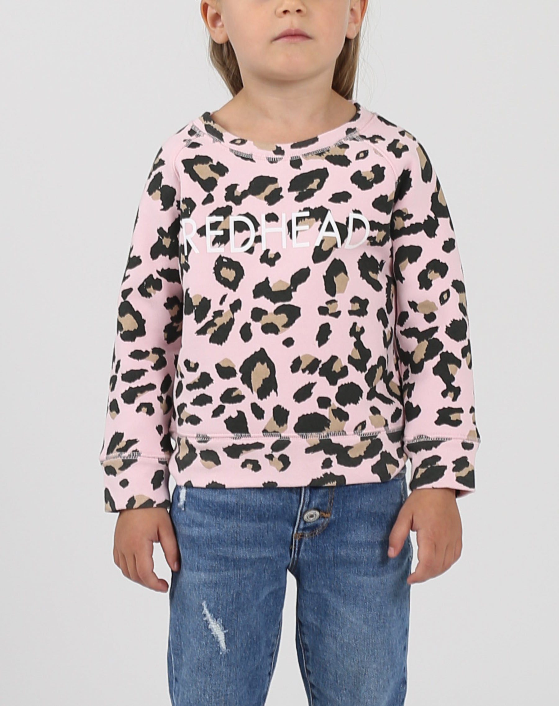 This is a photo of a model wearing the Little Babes Redhead Crew Neck Sweatshirt in Pink Leopard by Brunette The Label.
