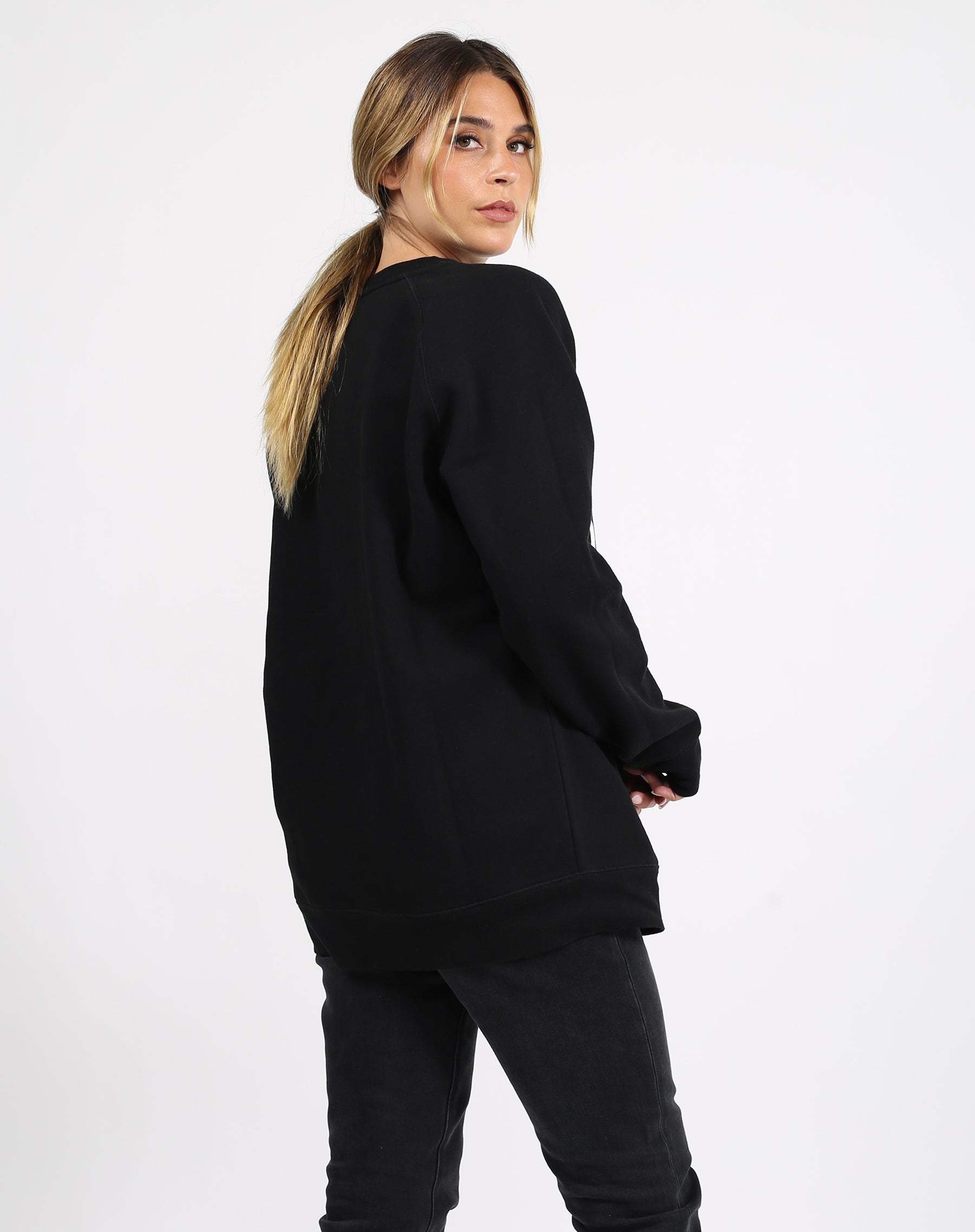 This is a photo of the back of a model wearing the Lounge Blonde Big Sister Crew Neck Sweatshirt in Black by Brunette the Label.'