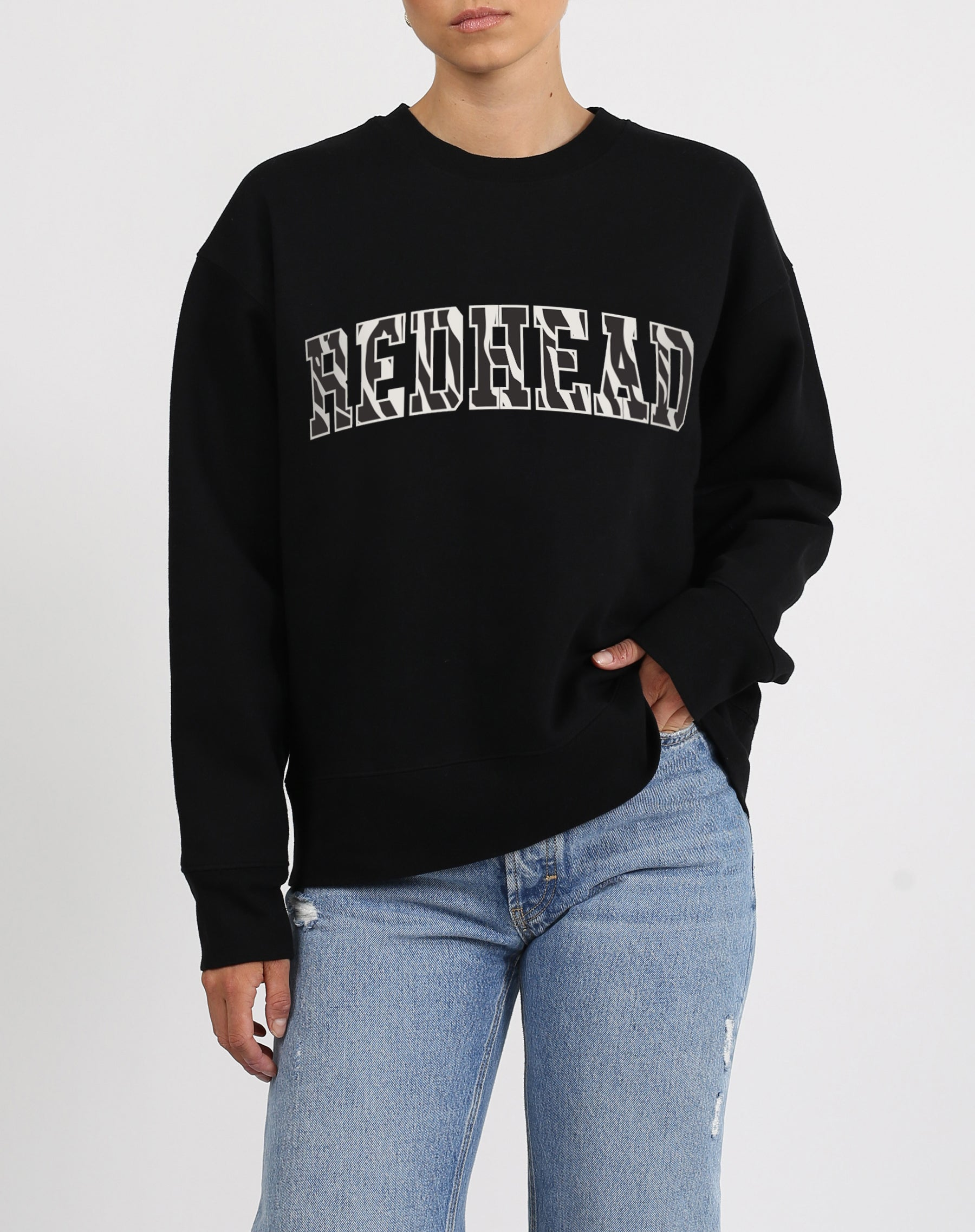 This is an image a model wearing the Redhead Zebra Varsity Step Sister Crew Neck Sweatshirt in Black by Brunette the Label.