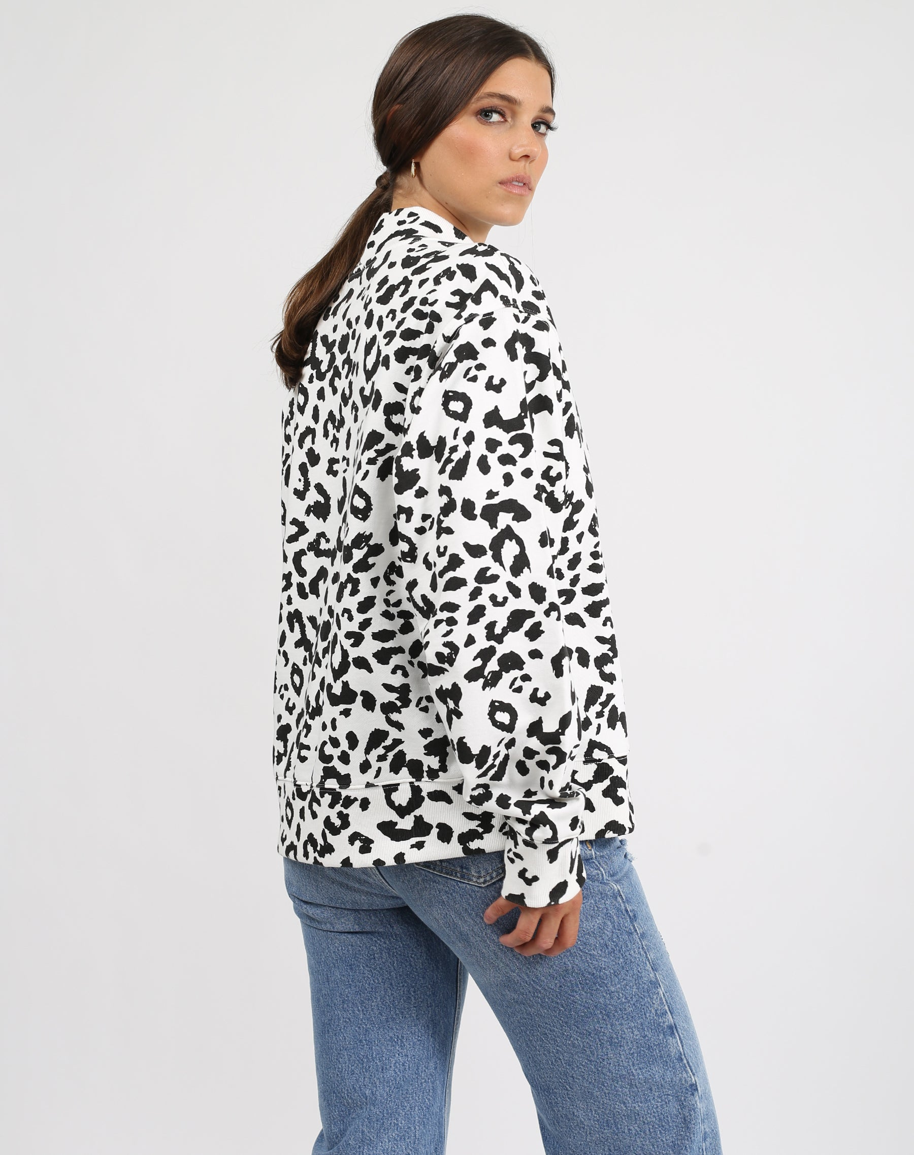 This is an image a model wearing the Step Sister Mock Neck Sweatshirt in Snow Leopard by Brunette the Label.