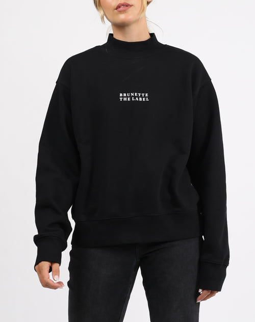 This is a photo of a model wearing the Step Sister Mock Neck Sweatshirt in Black by Brunette the Label.