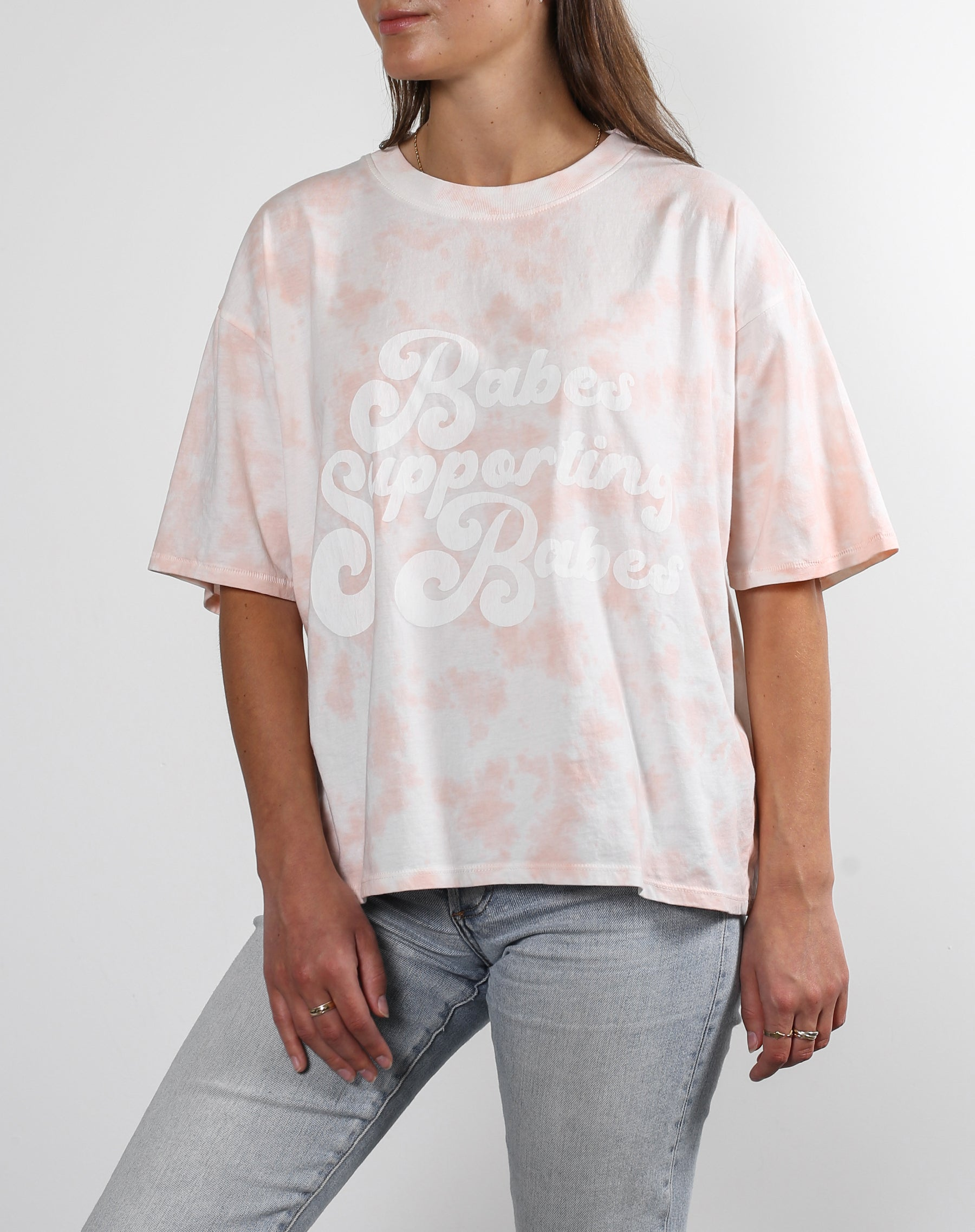 This is an Ecommerce photo of a model wearing the Babes Supporting Babes Boxy Crew Neck Tee in Pink Marble Dye