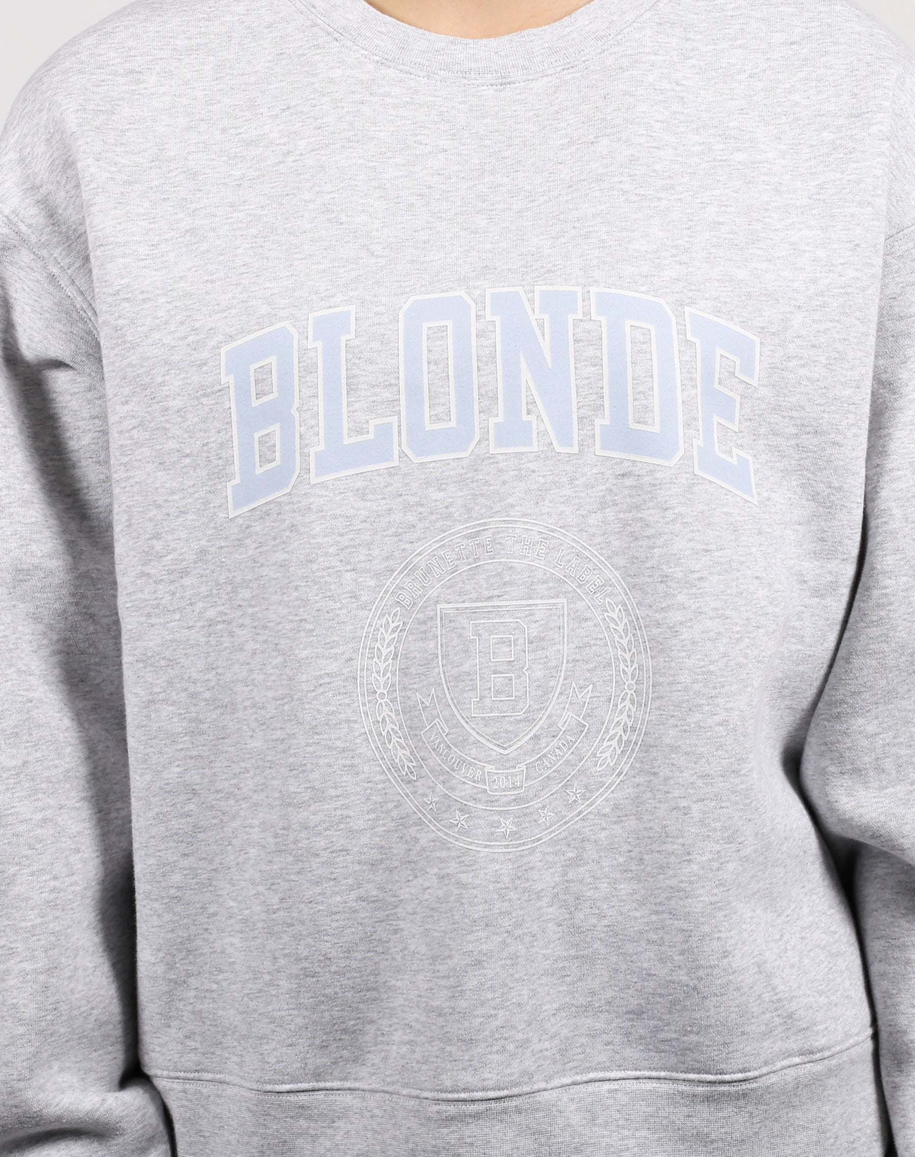 This is an image of the blonde varsity crest step sister crew neck sweatshirt in pebble grey from Brunette the Label