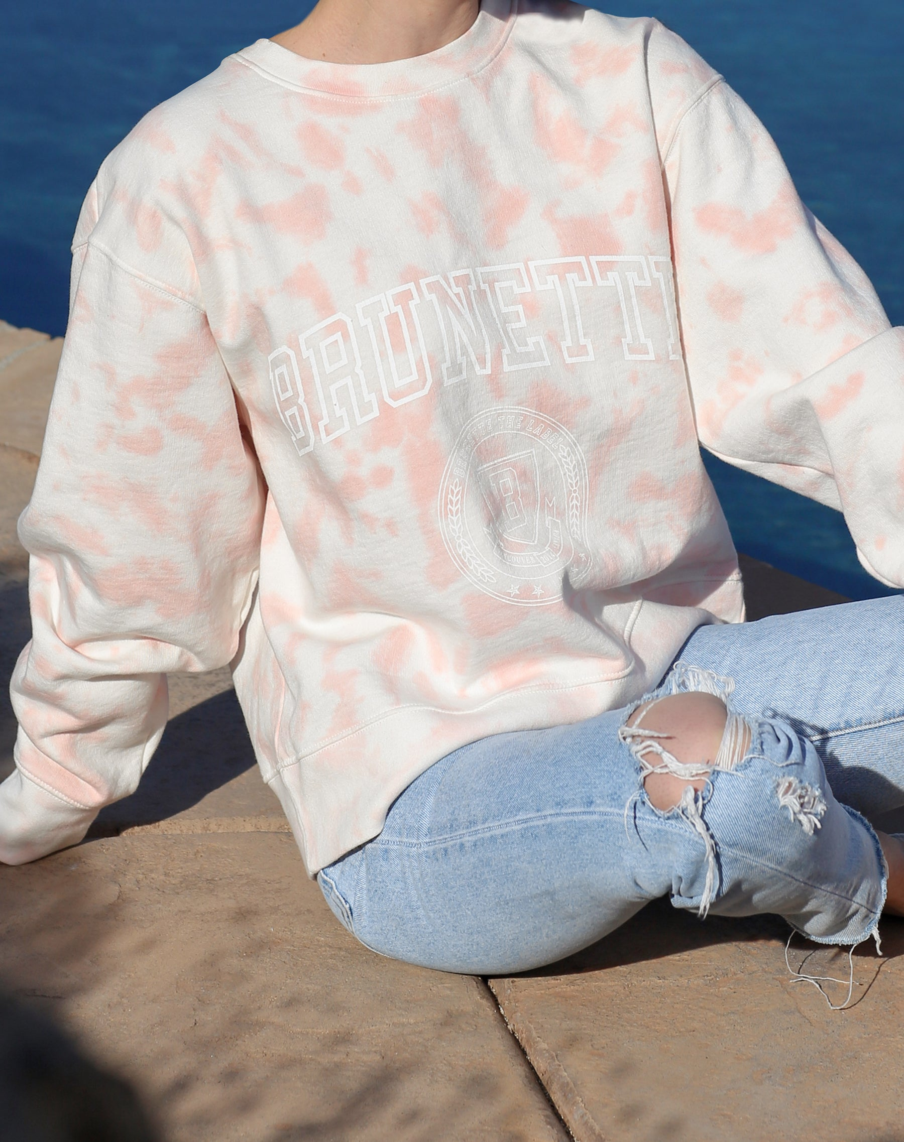 This is a campaign photo of the Brunette Step Sister Crew Neck Sweatshirt in Pink Marble Tie Dye