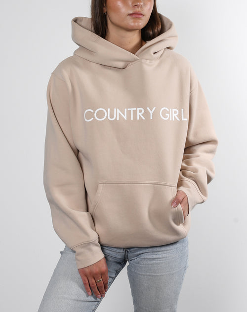 This is a photo of a model wearing the Classic Hoodie in toasted almond from the Monika Hibbs x brunette collaboration.