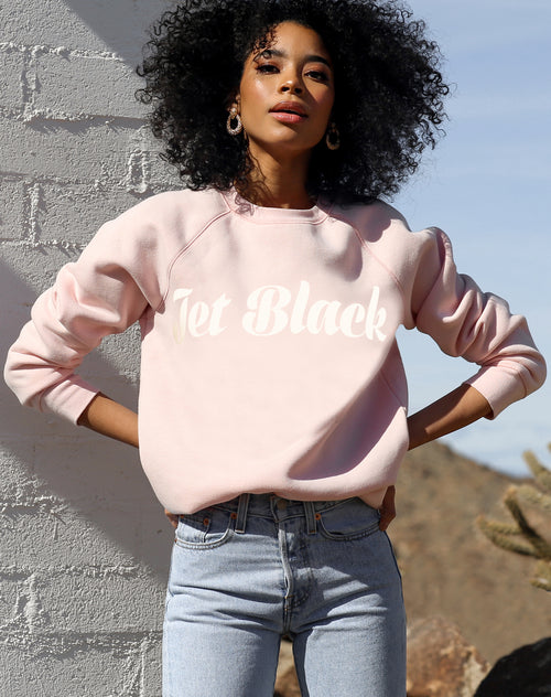 This is a photo of a model wearing the Jet Black Cursive Classic Crew in Ballet Slipper by Brunette the Label.