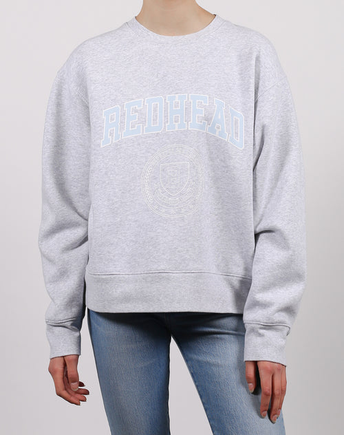 This is an image of the redhead varsity crest step sister crew neck sweatshirt in pebble grey from Brunette the Label
