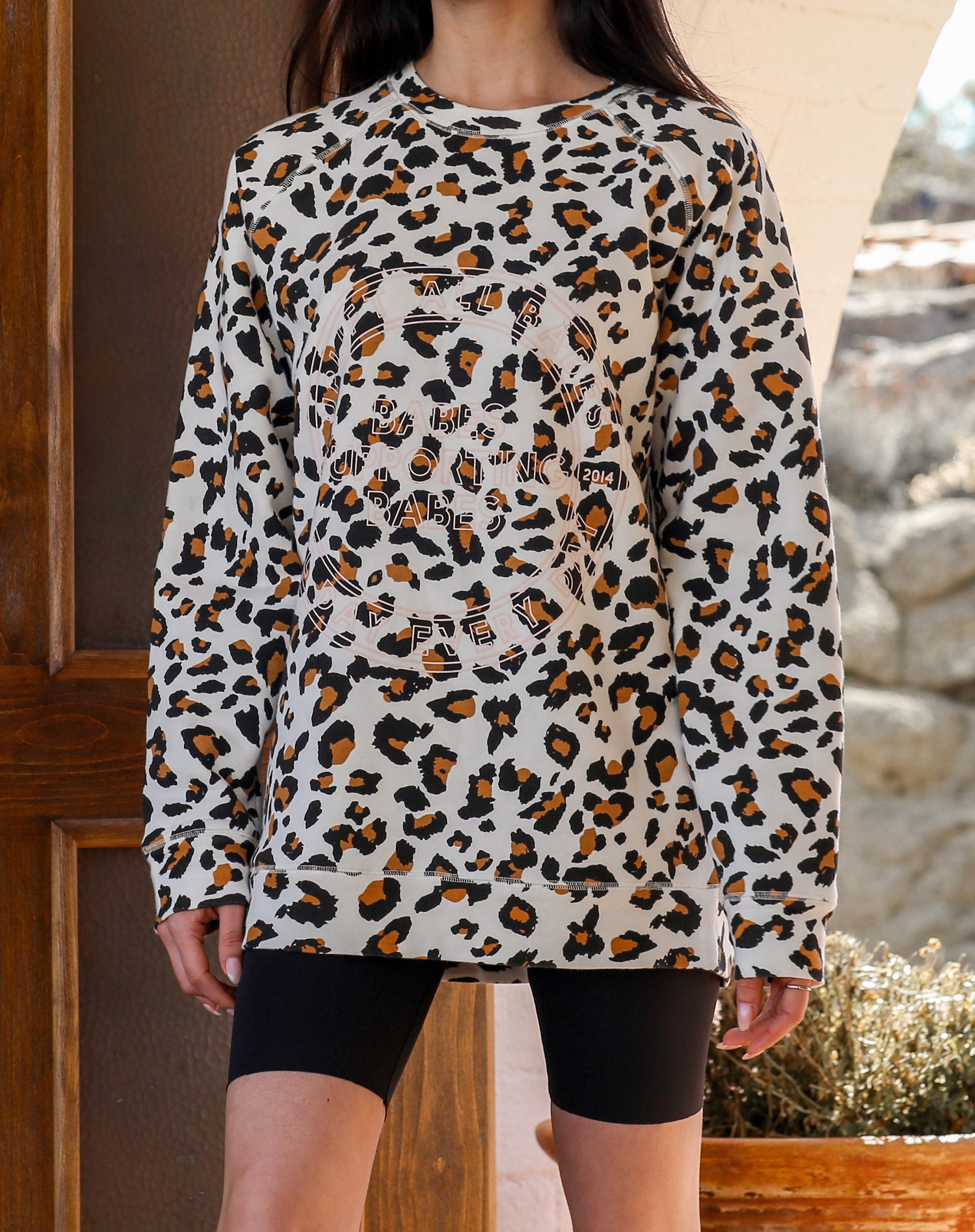 This is a campaign photo of the Uplift All Babes Big Sister Crew Neck Sweatshirt in White Leopard by Brunette the Label