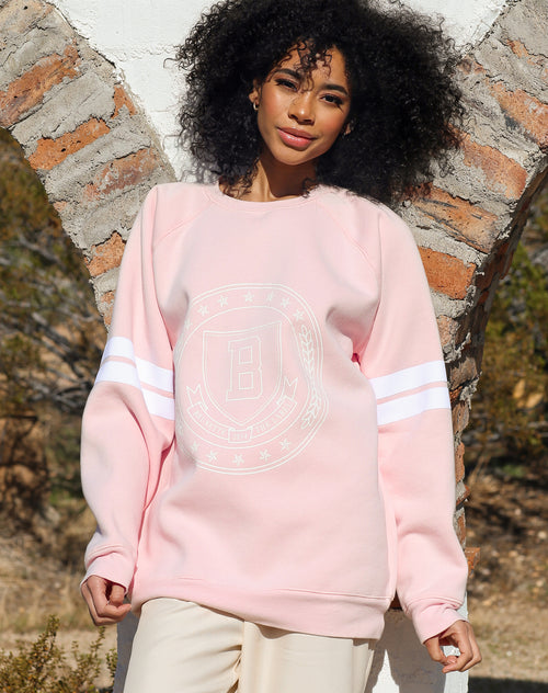 This is an image of the front of a campaign photo of the Varsity Crest Big Sister Crewneck Sweatshirt in Ballet Slipper from Brunette the Label