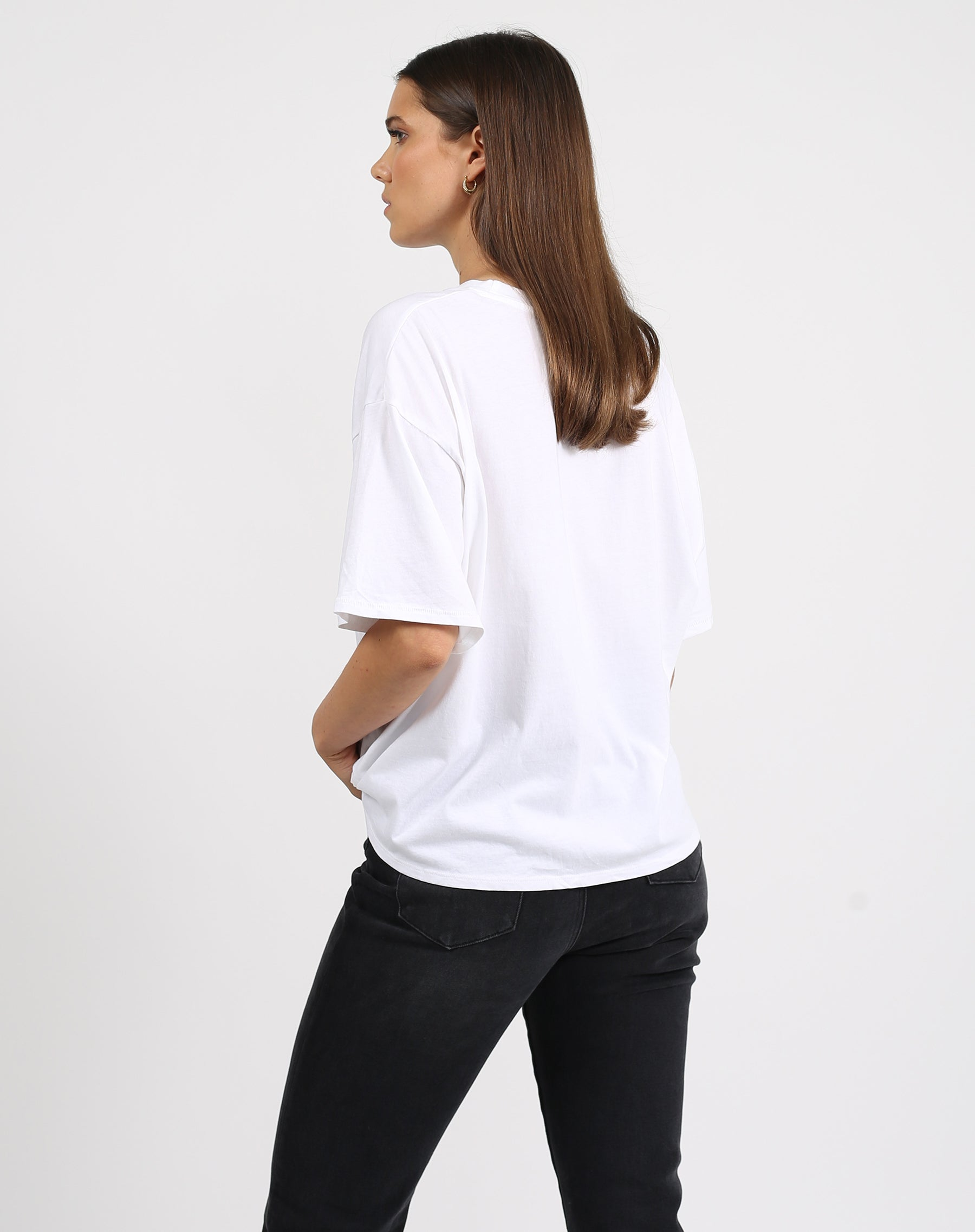 This is a photo of the back of a model wearing the welcome to the babes club boxy tee crew neck in white by brunette the label.