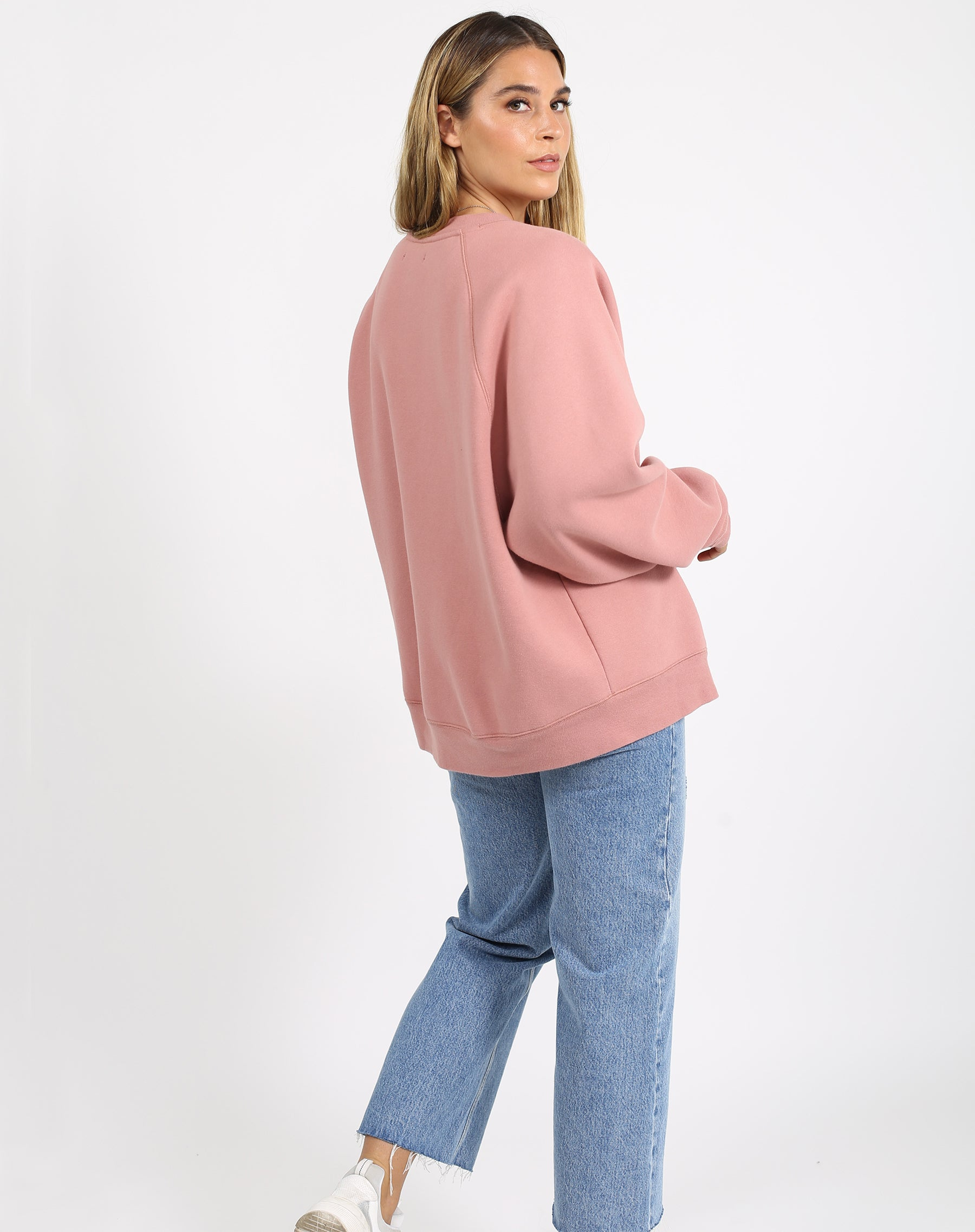 This is a photo of the side of a model wearing the welcome to the babes club not your boyfriend fit crew neck sweatshirt in vintage rose by brunette the label.