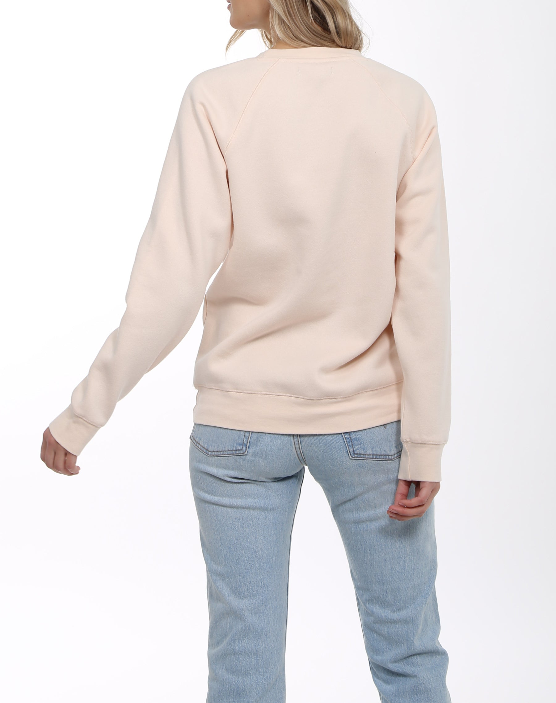 Photo of the back of the Redhead classic crew neck sweatshirt in peach crush by brunette the label.