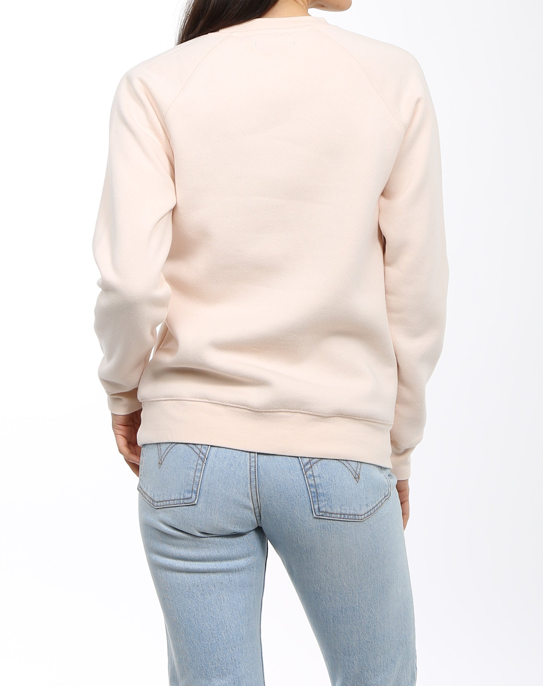 The back of a model photographed wearing the Brunette Crew Neck Sweatshirt in Peach Crush by Brunette the Label.
