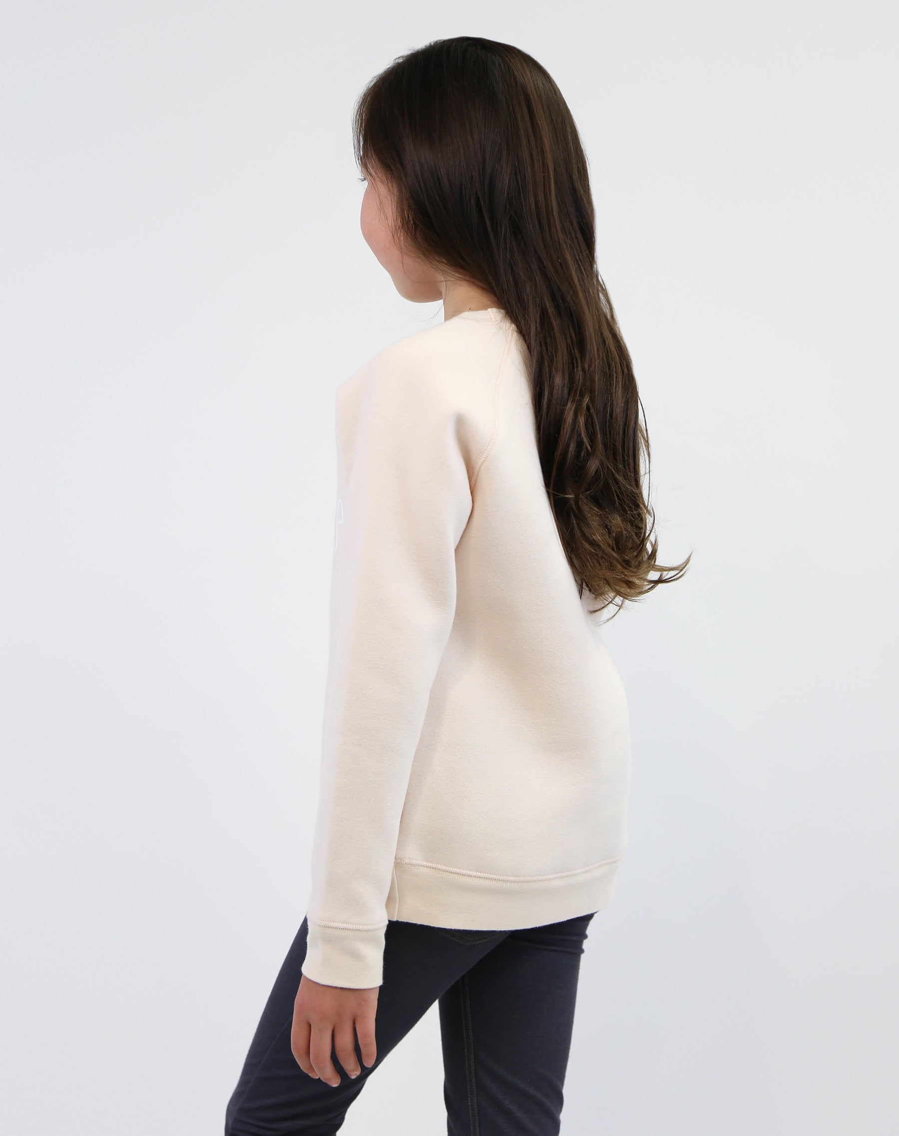Back photo of child wearing the We Are All Babes classic crew neck sweatshirt in peach crush by Brunette the Label.