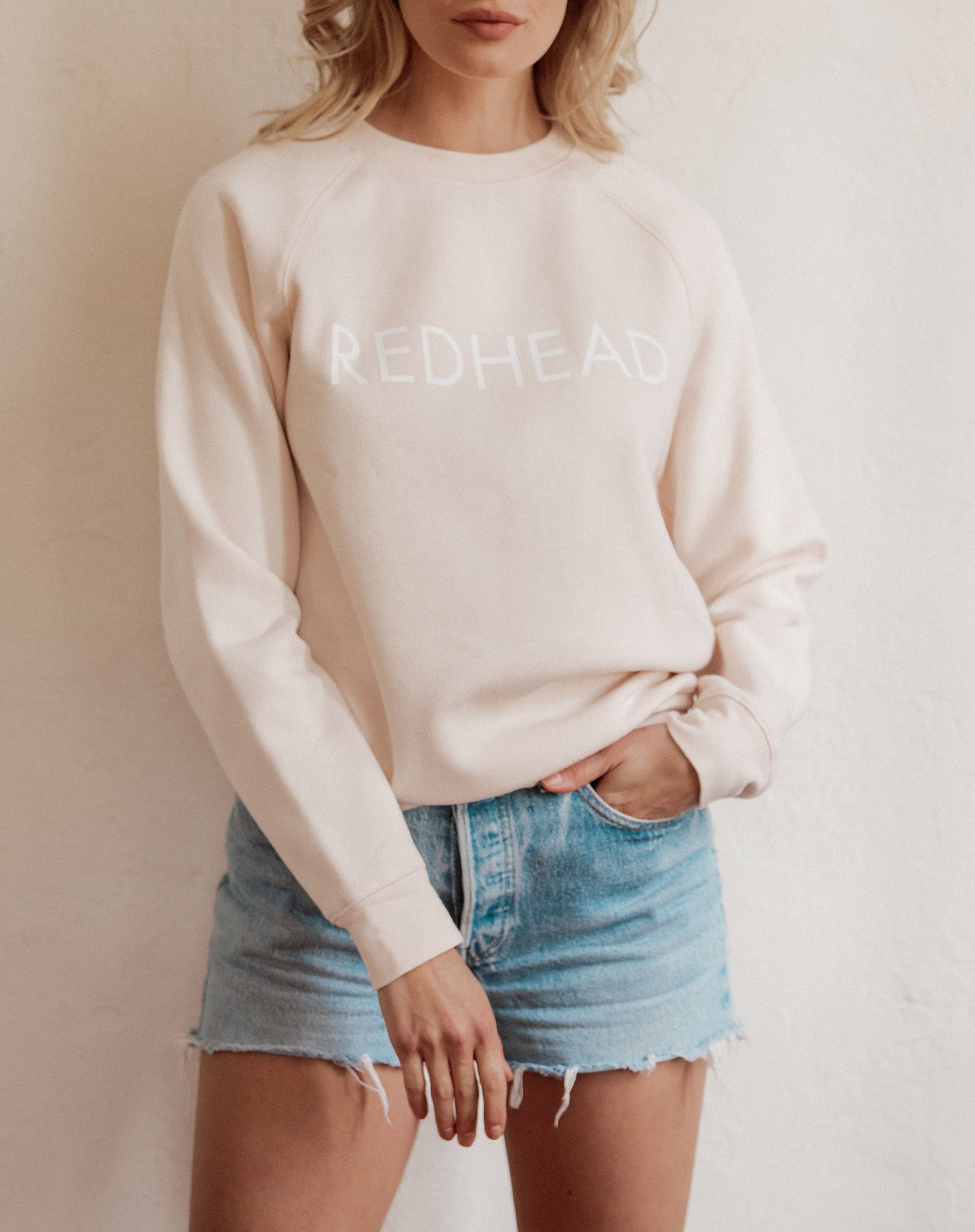 Photo of the Redhead classic crew neck sweatshirt in peach crush by brunette the label.