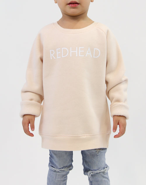 Photo of child wearing the Redhead classic crew neck sweatshirt in peach crush by Brunette the Label.