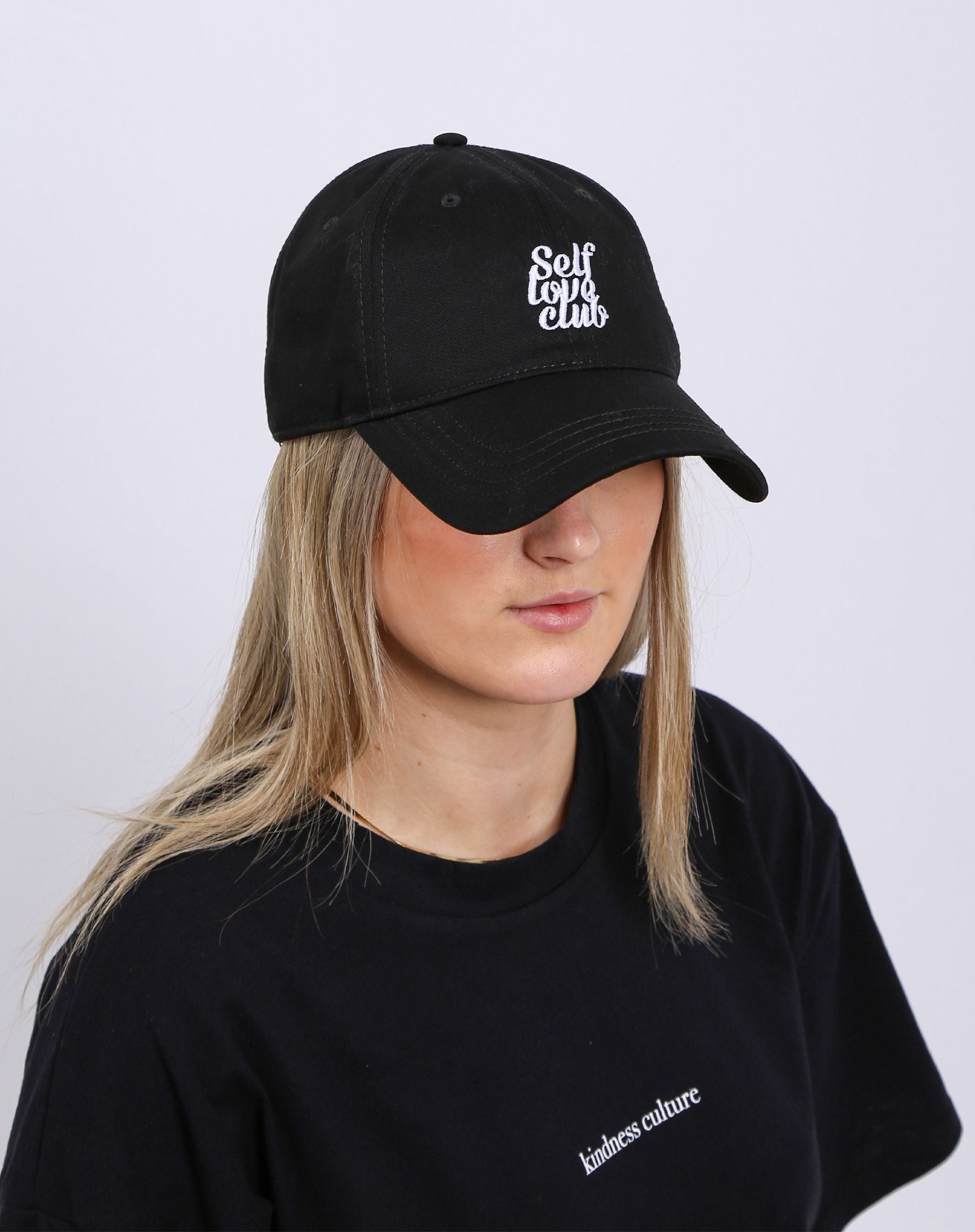 This is a photo of a model wearing the self love club baseball cap in black.